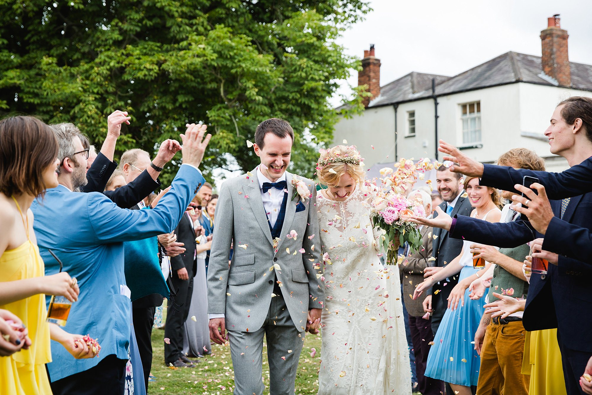 Isis Farmhouse Oxford Wedding bride and groom walking through thrown confetti