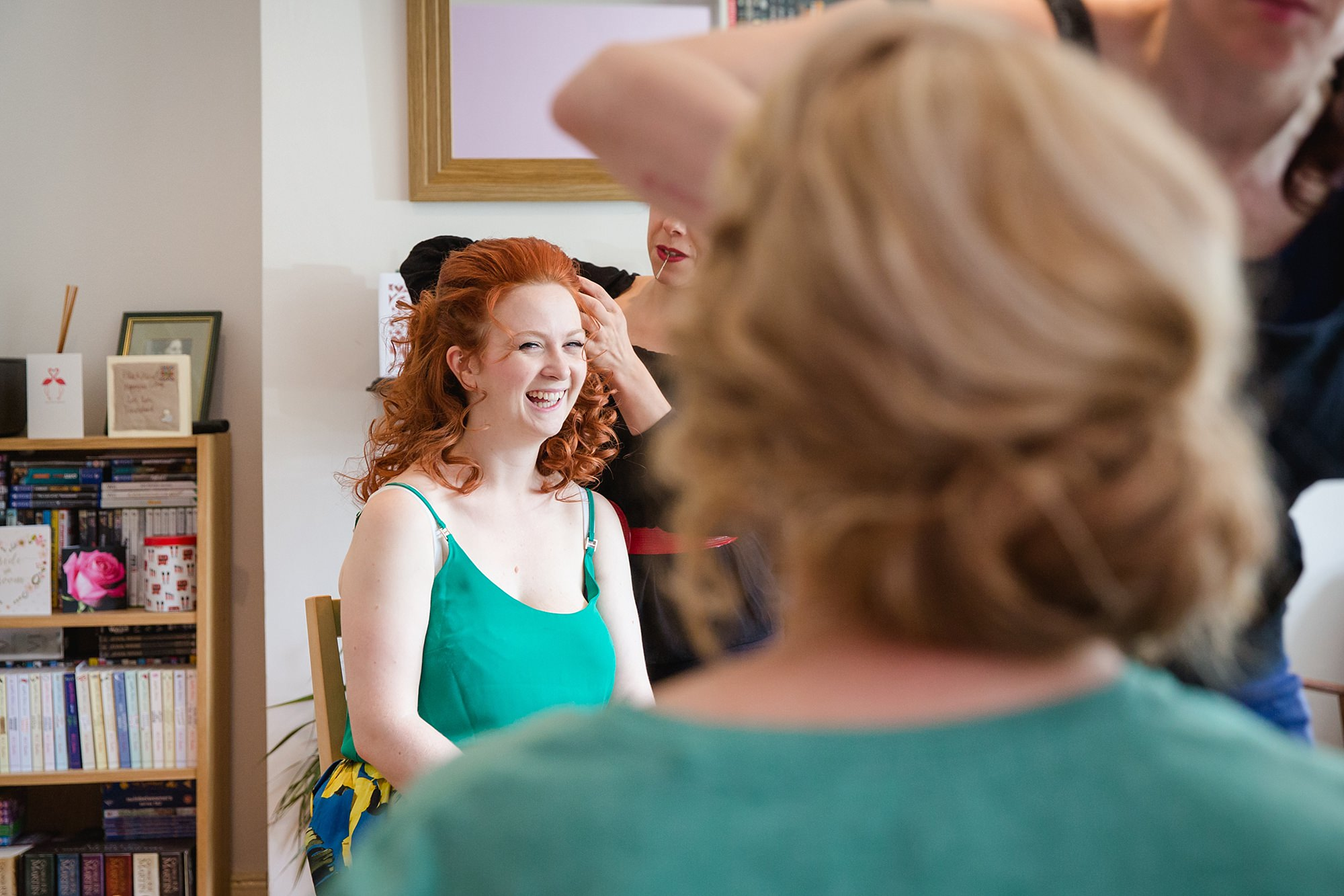 oyster shed wedding a bride smiles has she has her hair styled