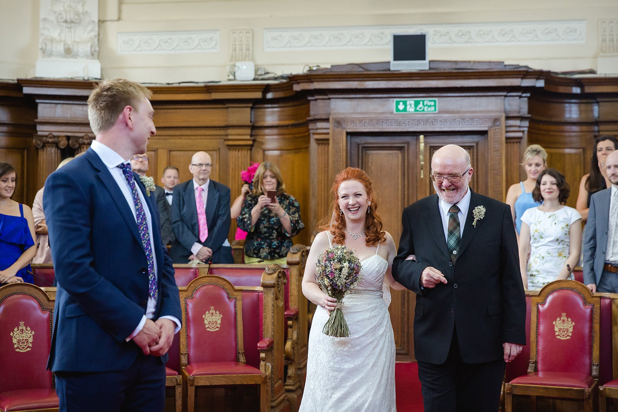 oyster shed wedding bride smiles as she walks down the aisle at islington town hall