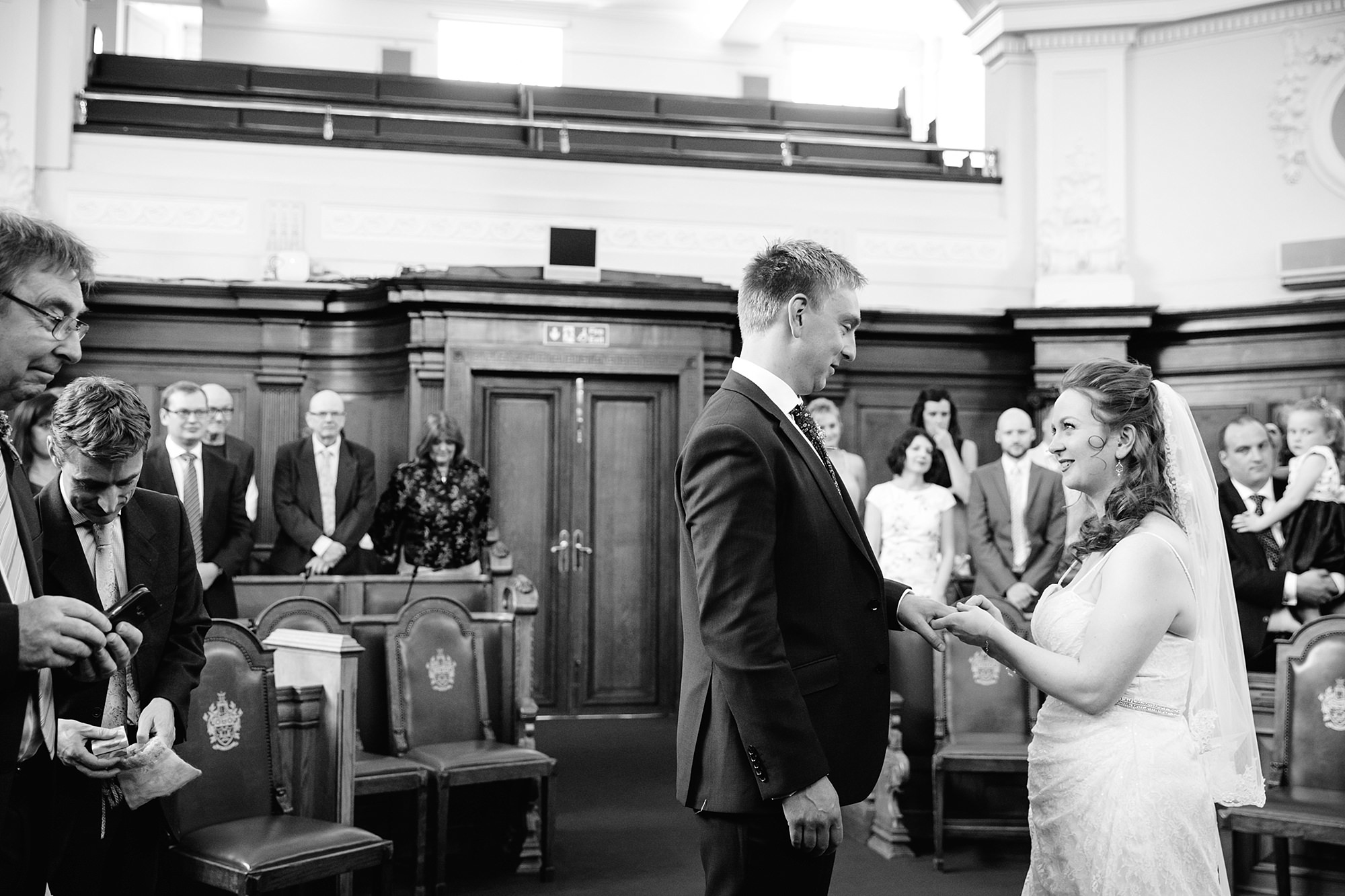 oyster shed wedding bride and groom exchange rings at islington town hall