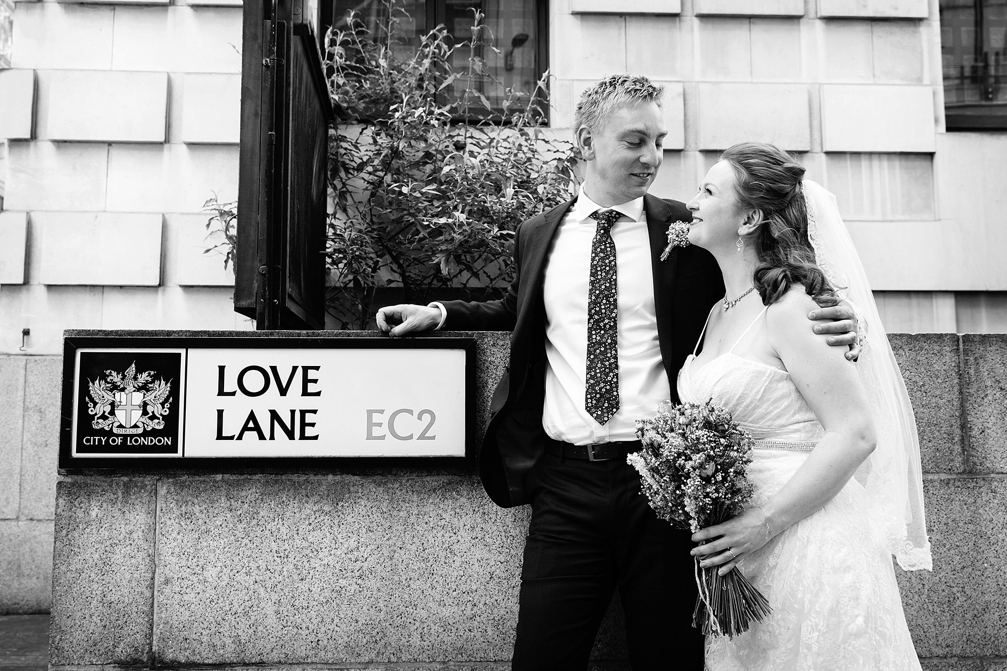 oyster shed wedding bride and groom laugh together by love lane sign