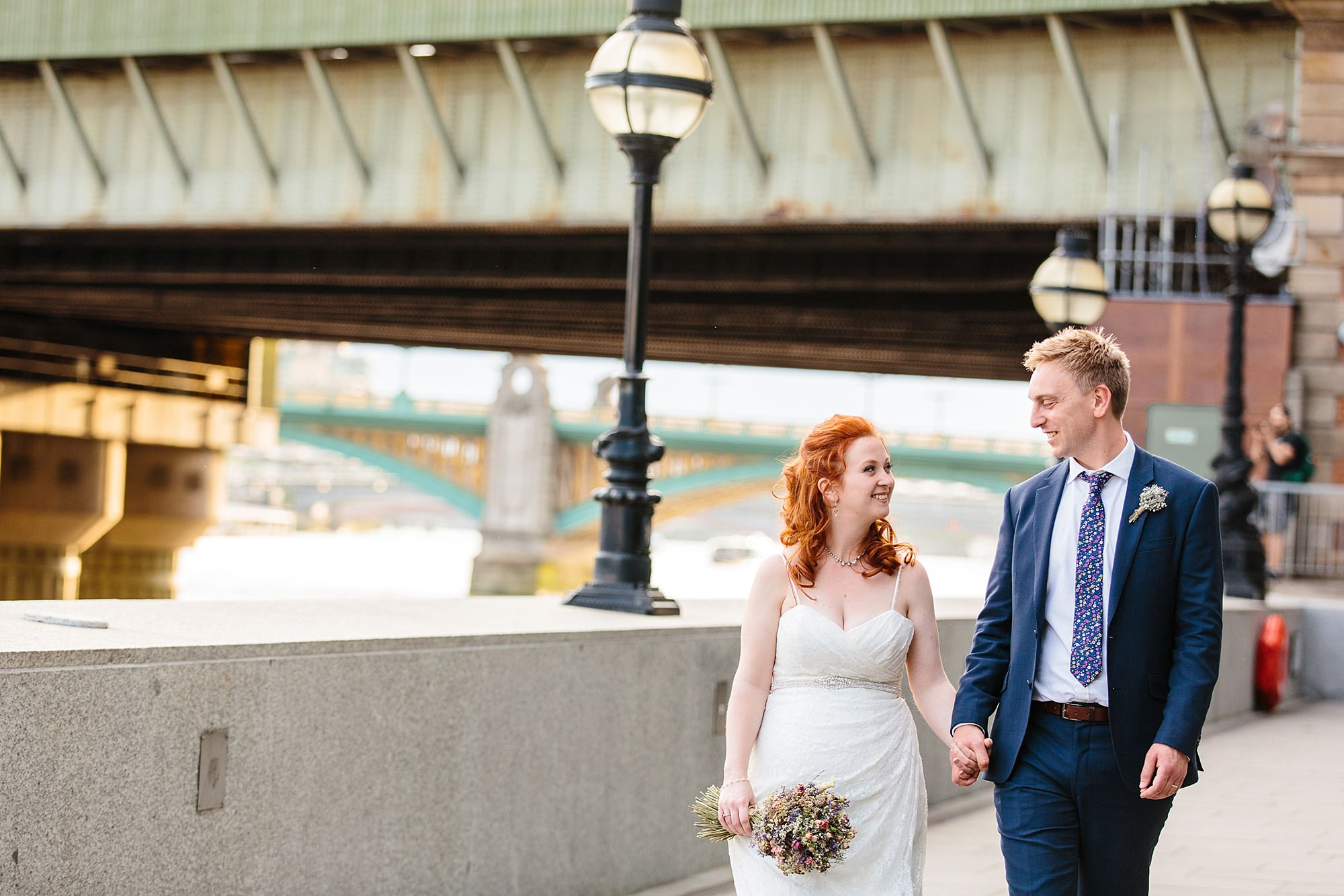 oyster shed wedding portrait of bride and groom walking by the thames