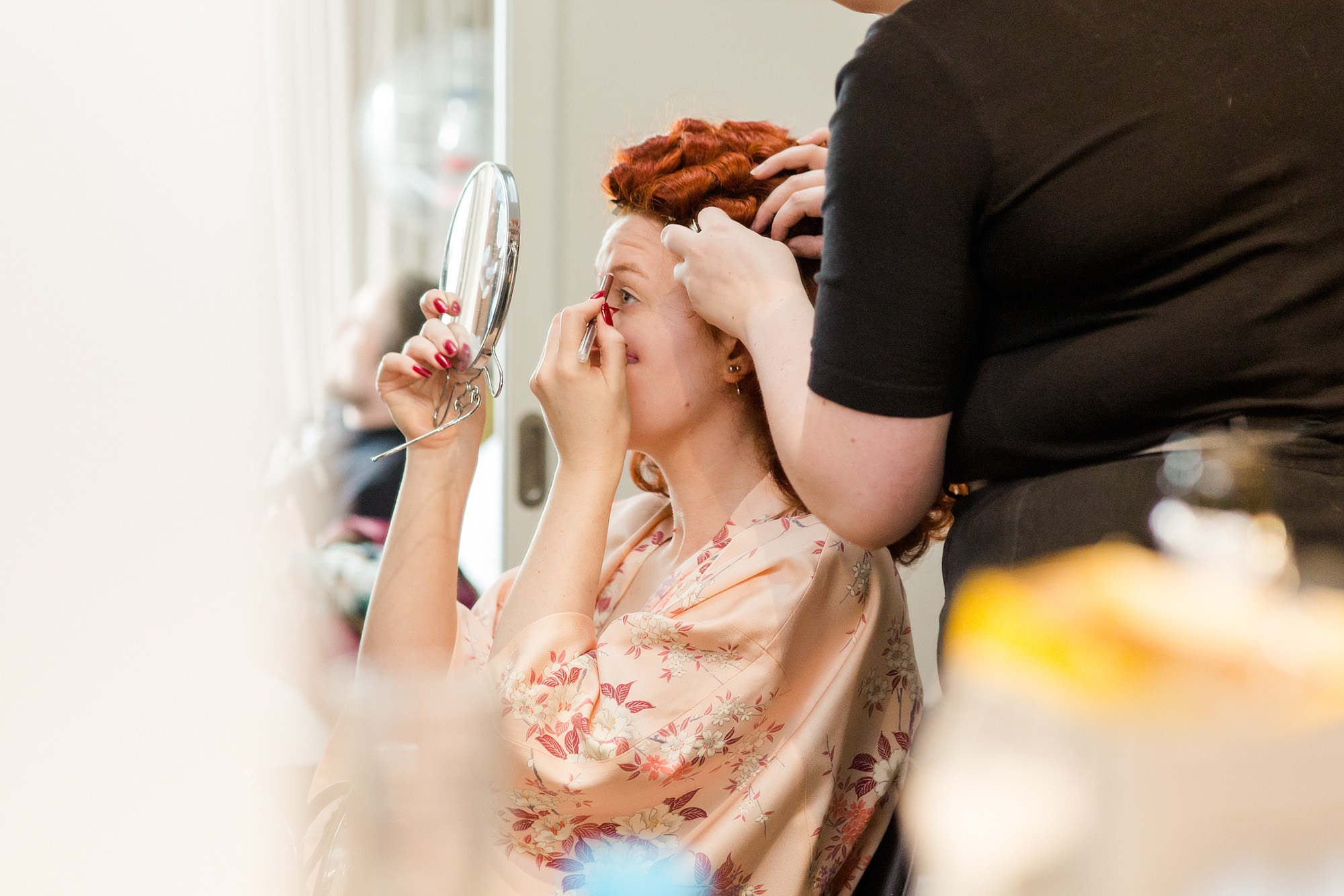 The Grange Ealing wedding bride does her makeup while her hair is being styled