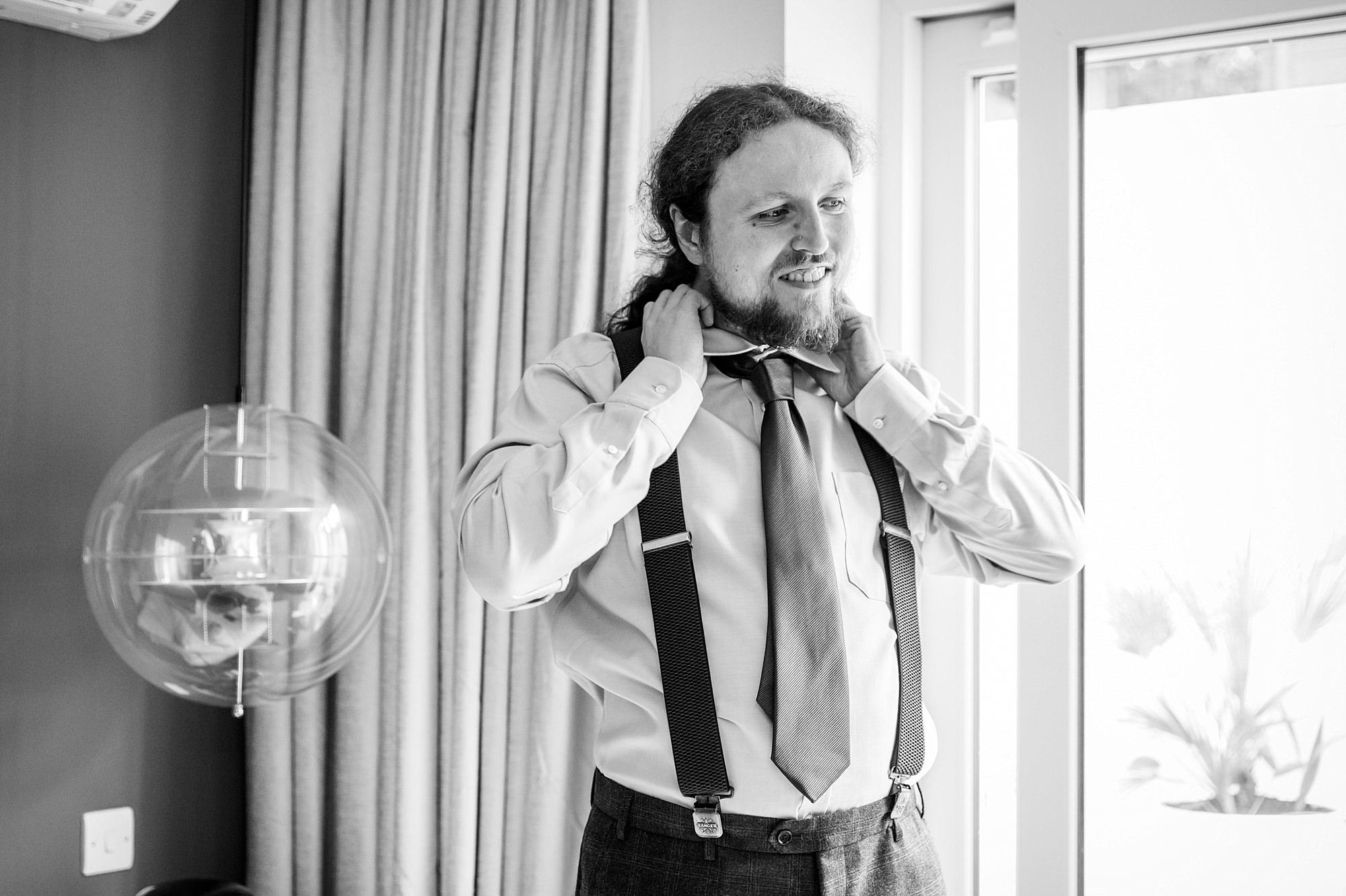 The Grange Ealing wedding portrait of groom tying his tie