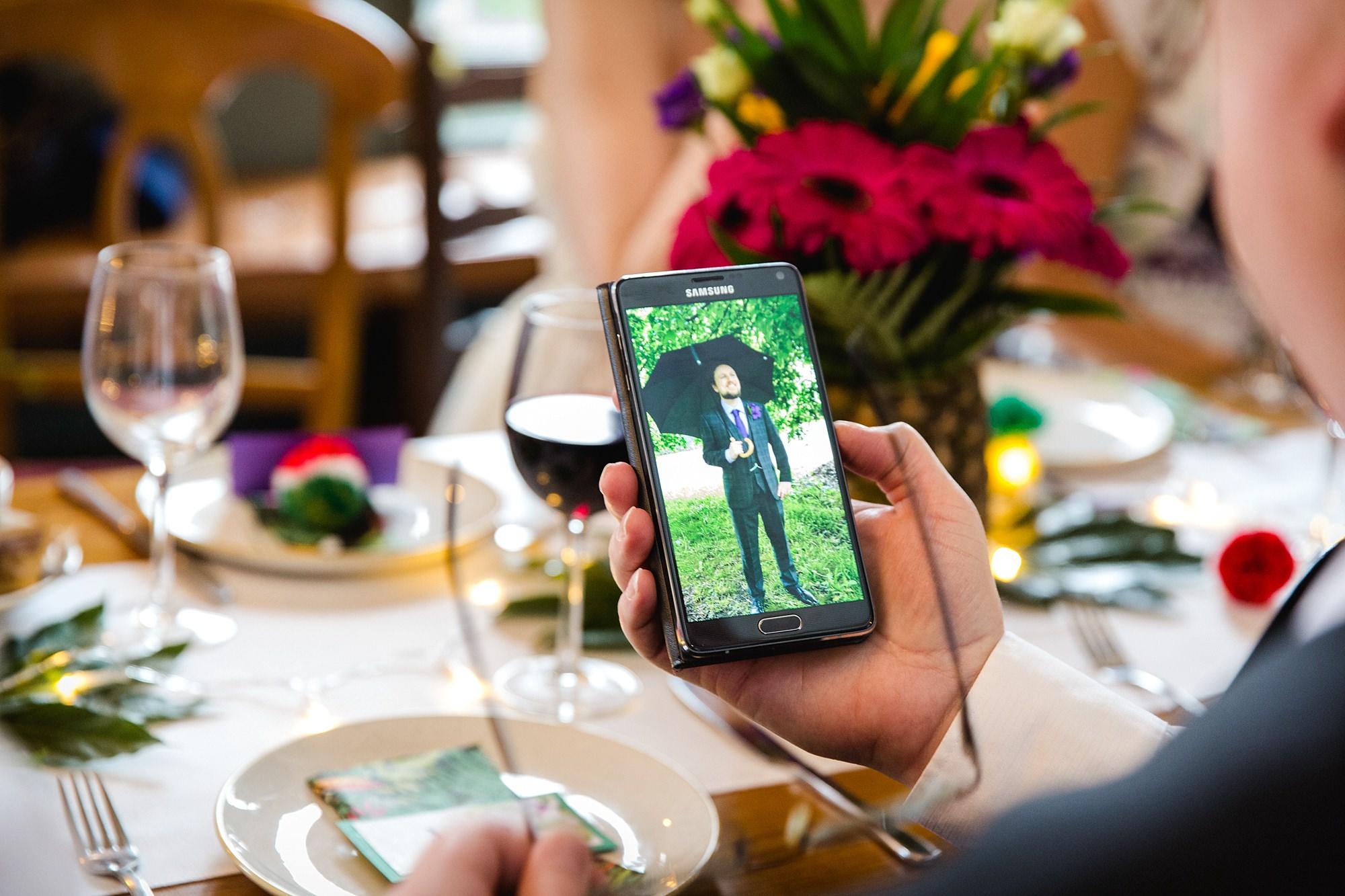 The Grange Ealing wedding portrait of groom on mobile phone