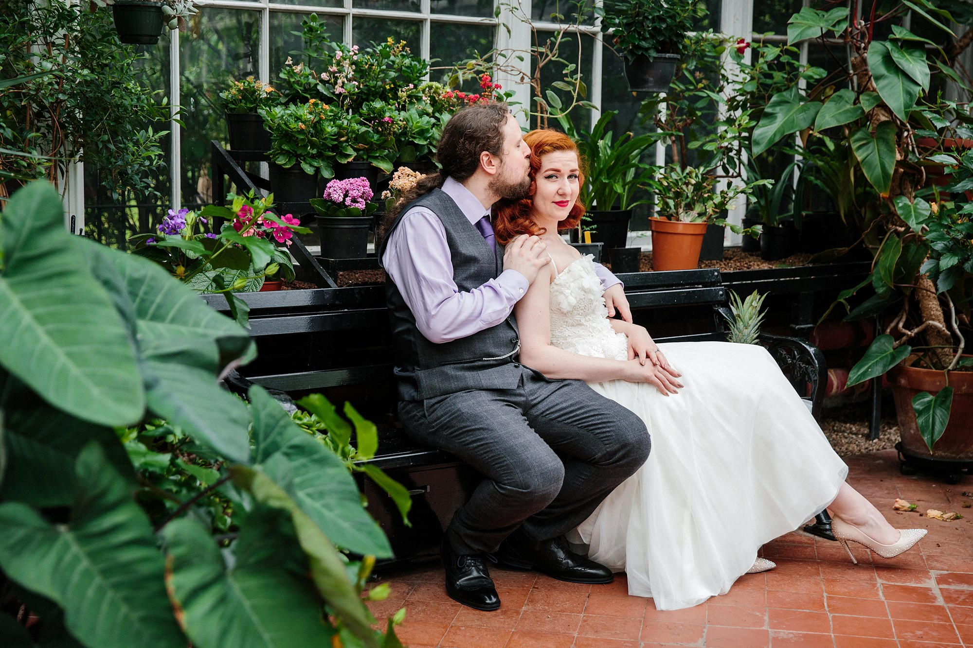tropical wedding shoot portrait of groom and bride on bench in conservatory