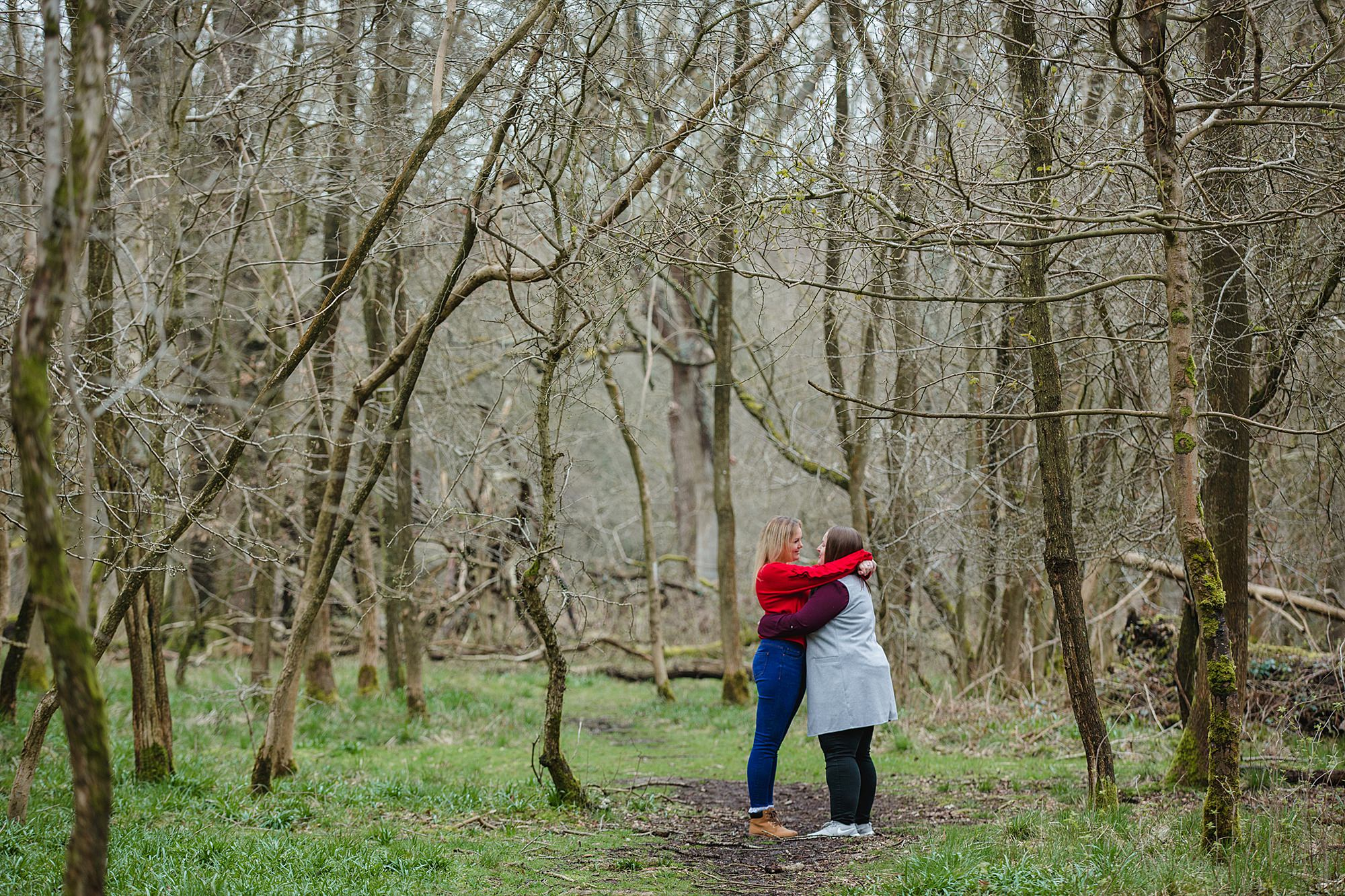 Ashridge park engagement shoot brides hug each other by treee