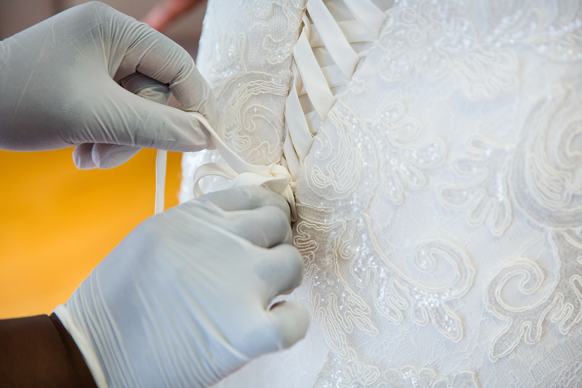 Bank of England Sports Centre wedding close up detail of bride's dress being tied