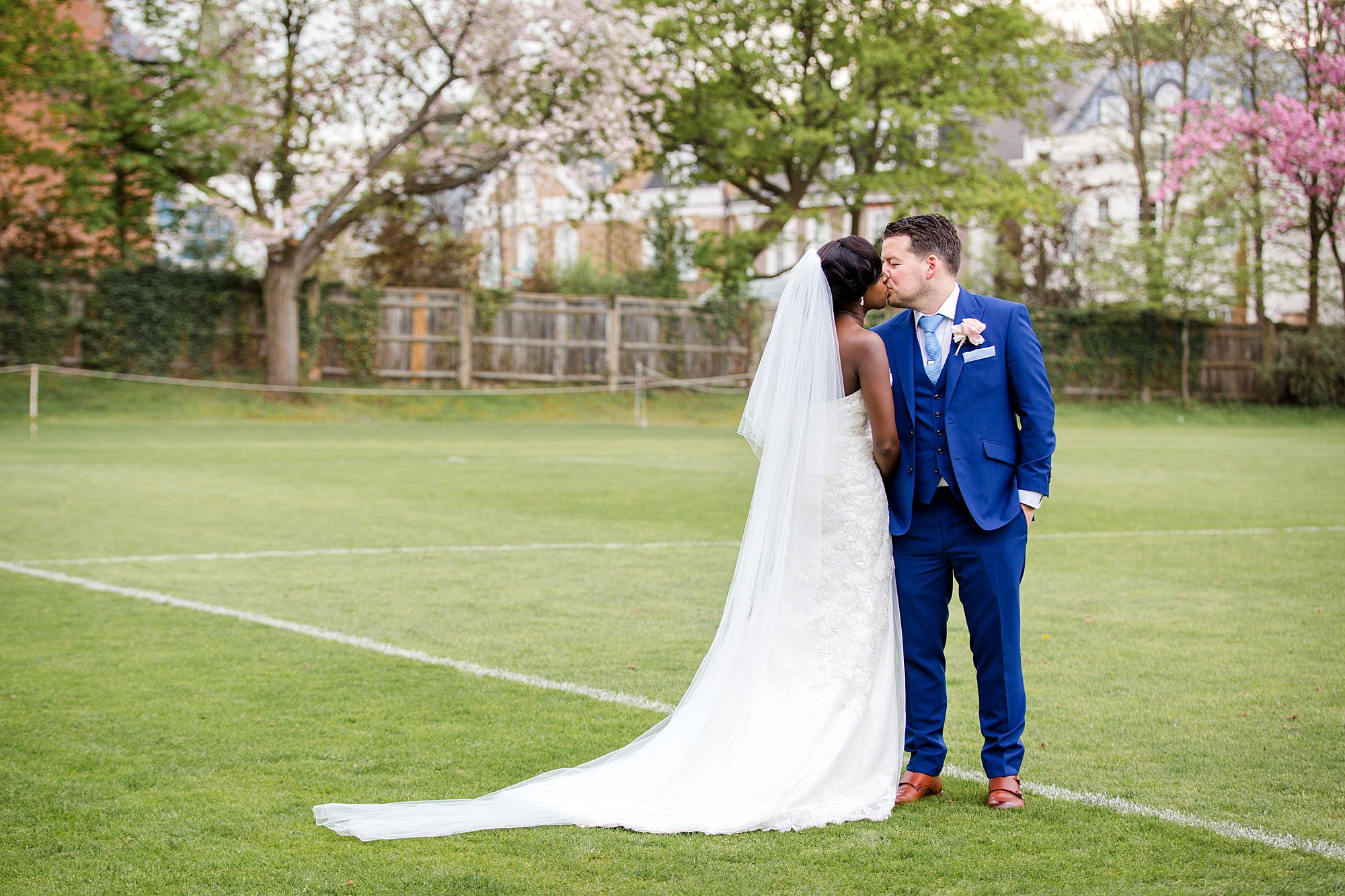 Bank of England Sports Centre wedding groom and bride kiss on field