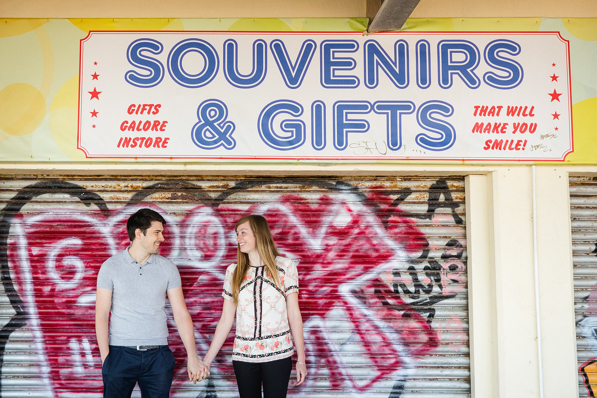 Fun Brighton engagement shoot couple in front of souvenir sign