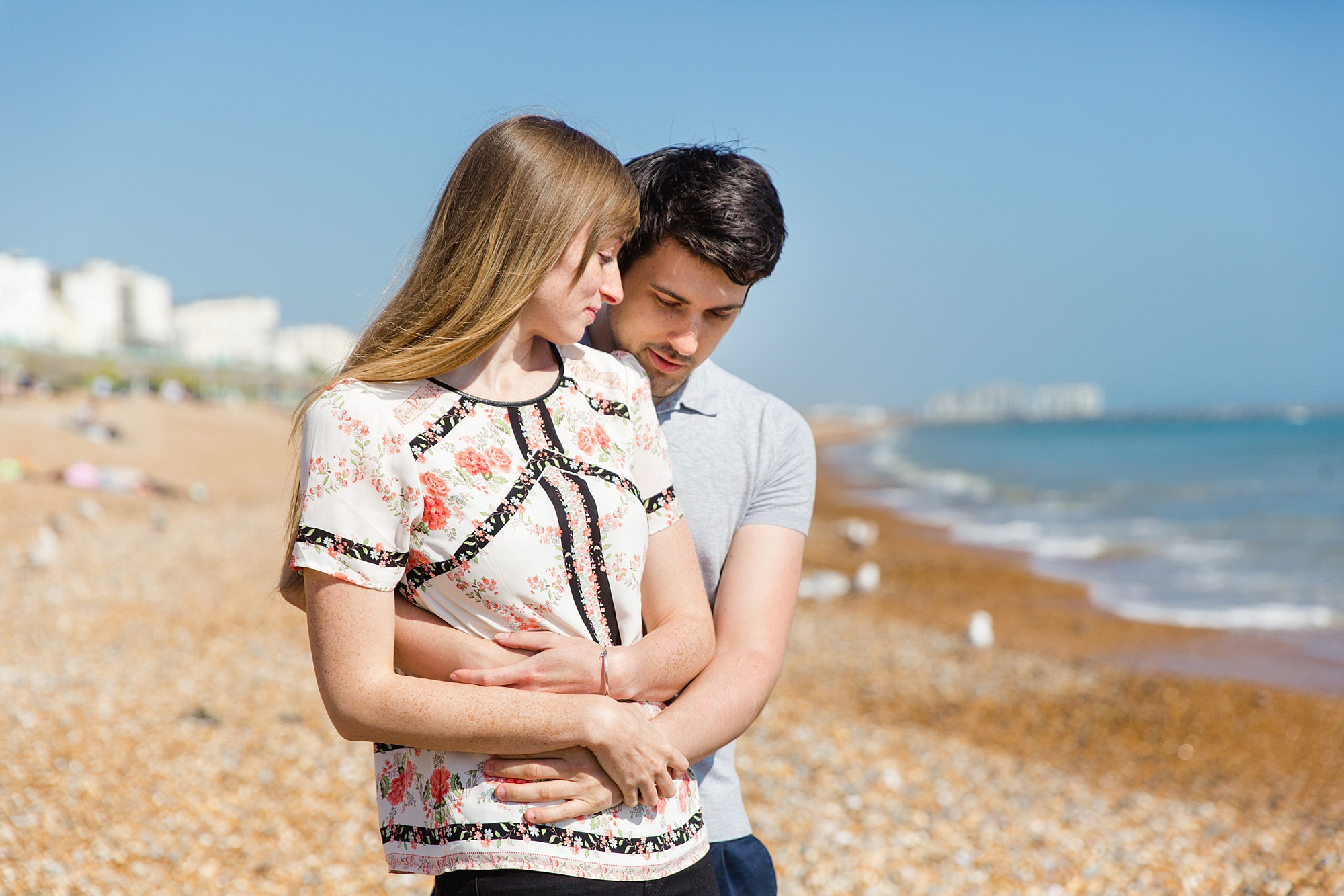 Fun Brighton engagement shoot couple cuddle on beach
