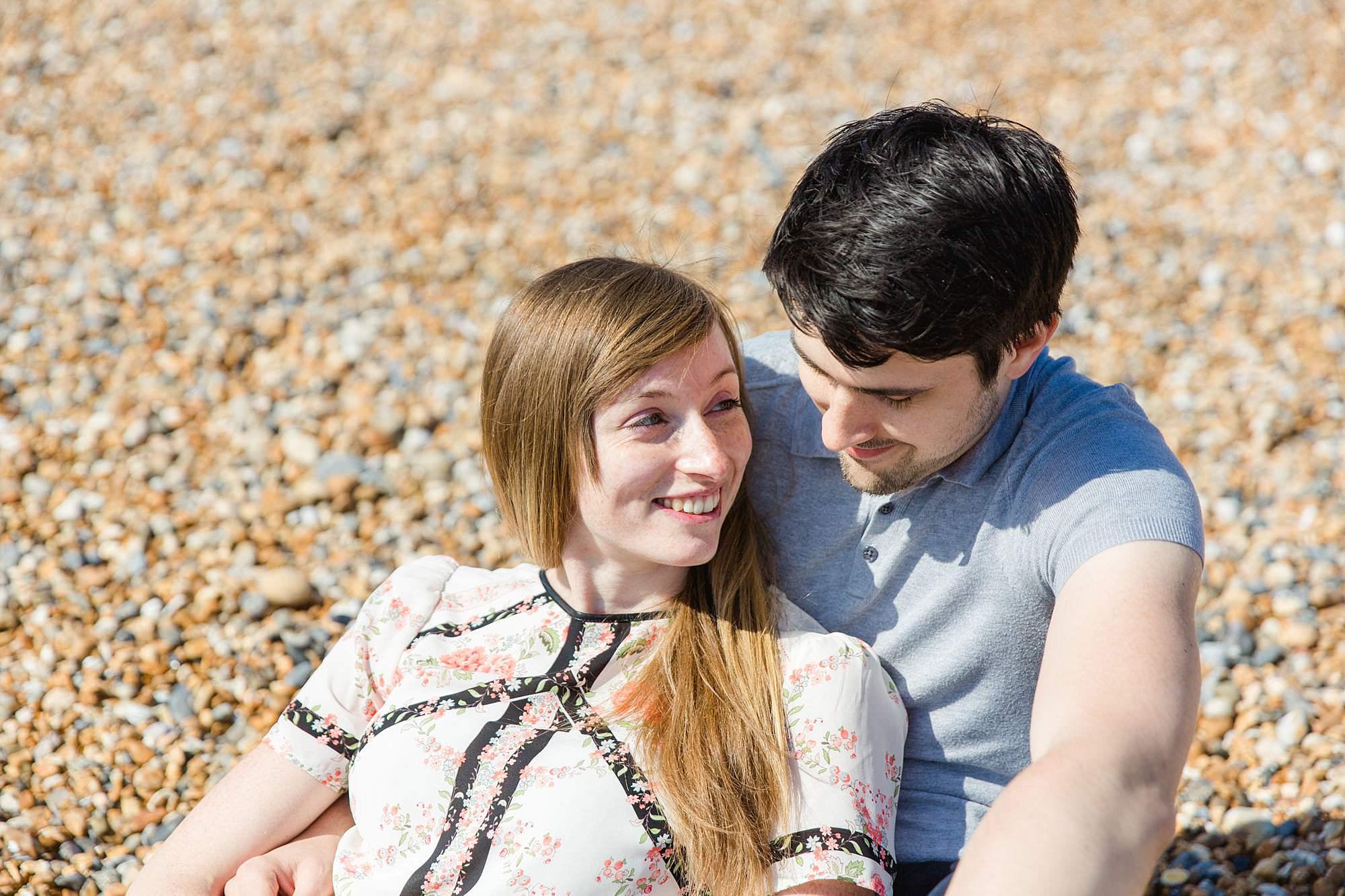 Fun Brighton engagement shoot couple sitting on beach