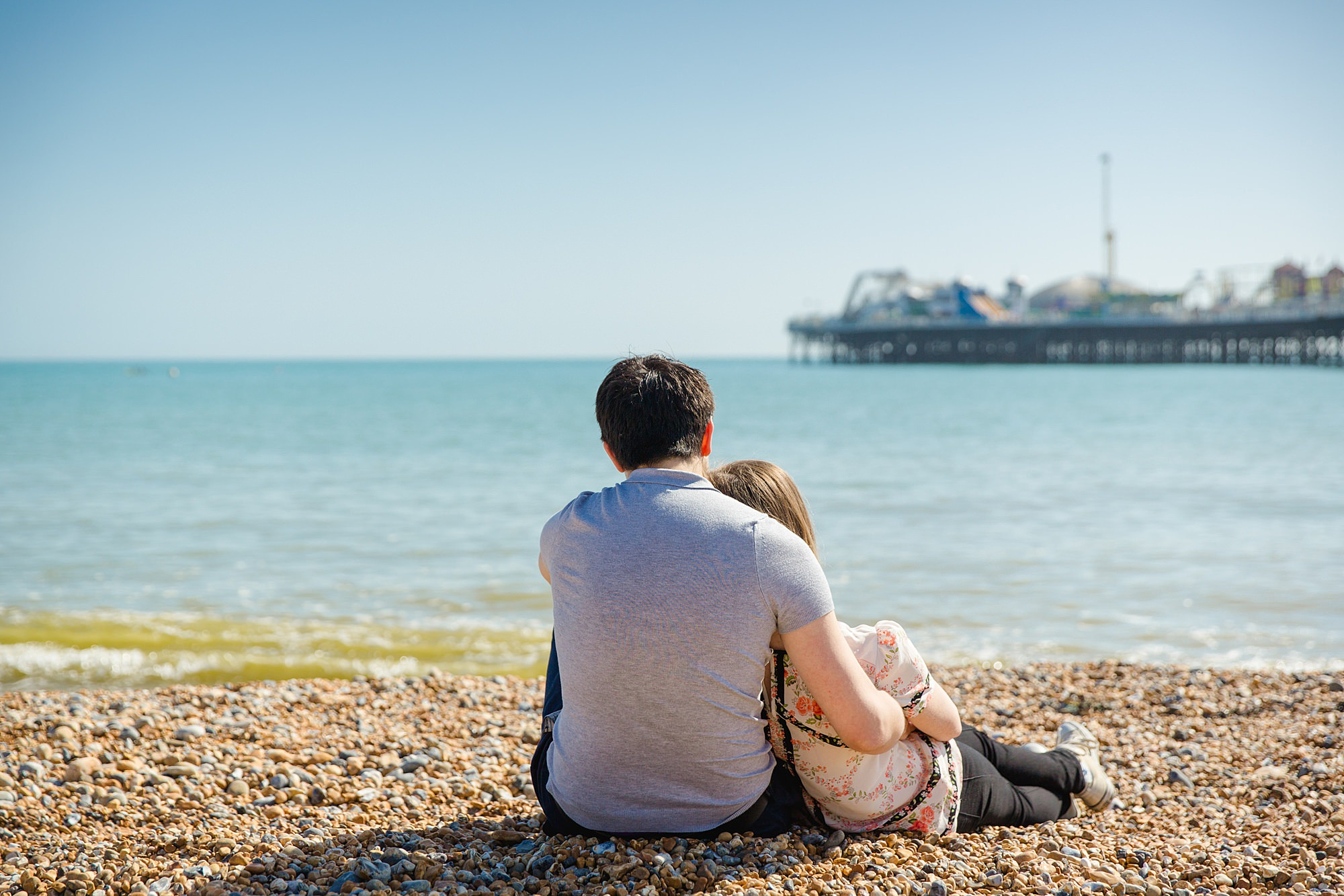 Fun Brighton engagement shoot couple sit together on beach