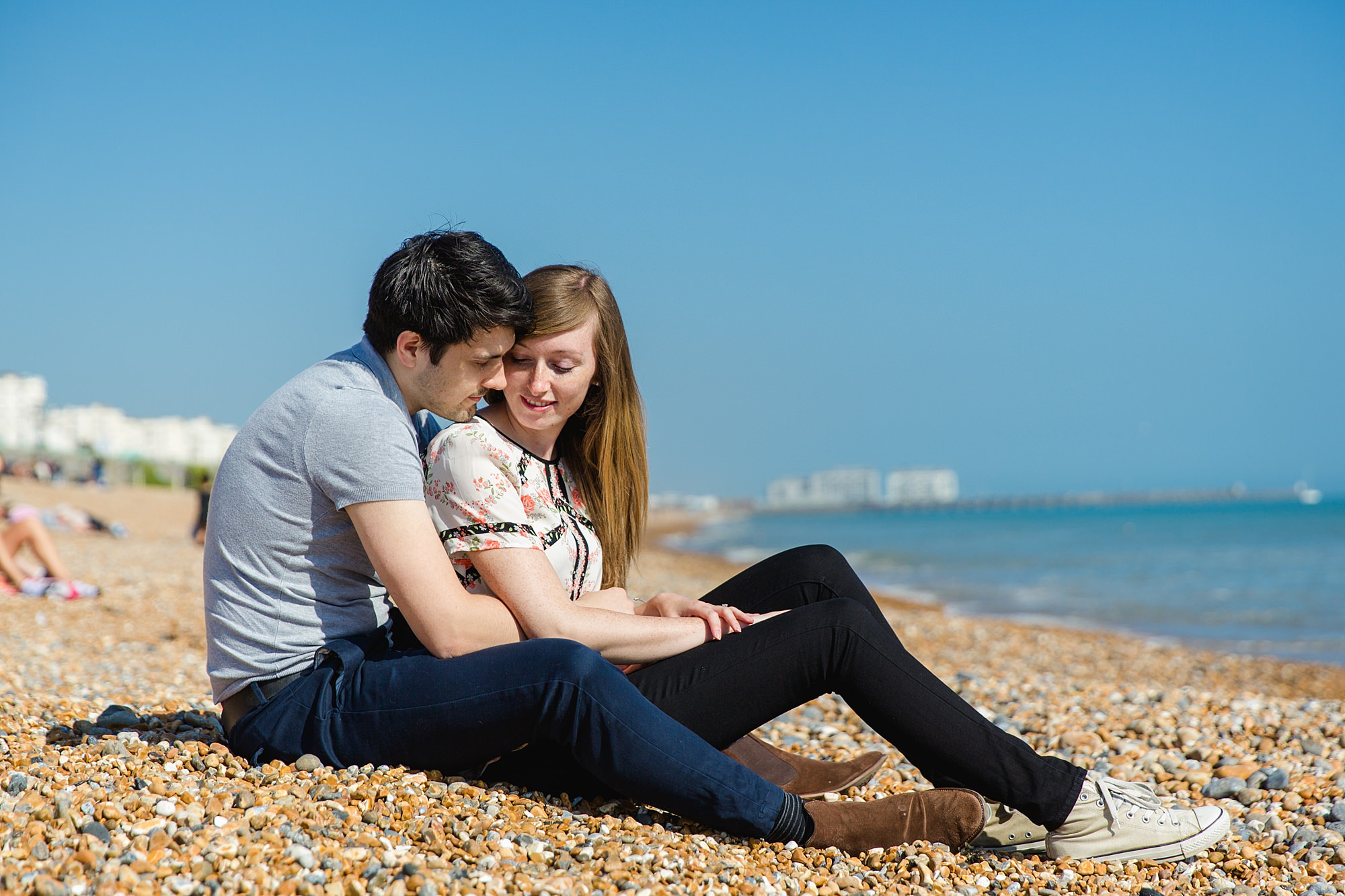 Fun Brighton engagement shoot couple sit and cuddle on beach