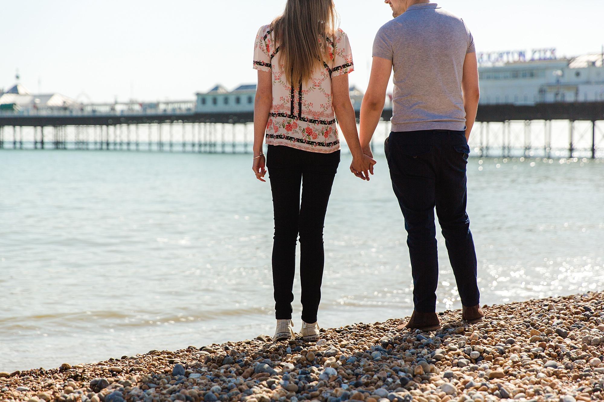 Fun Brighton engagement shoot brighton couple standing on beach