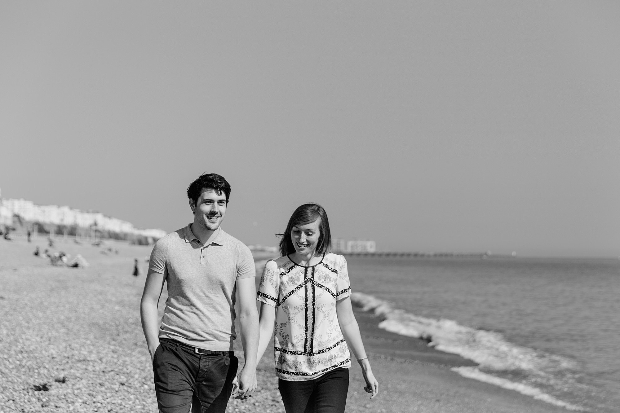 Fun Brighton engagement shoot portrait of couple walking along beach