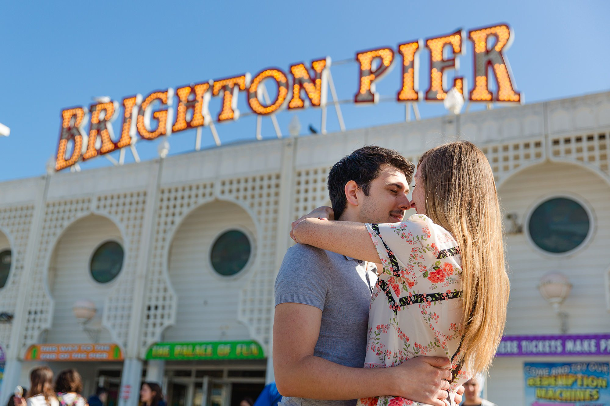 Fun Brighton engagement shoot couple in front of brighton pier sign