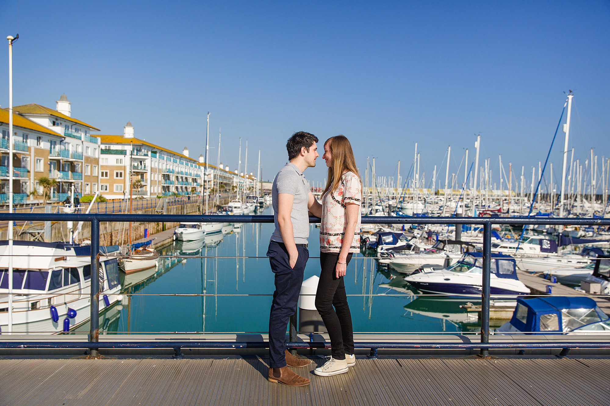 Fun Brighton engagement shoot couple stood together in harbour