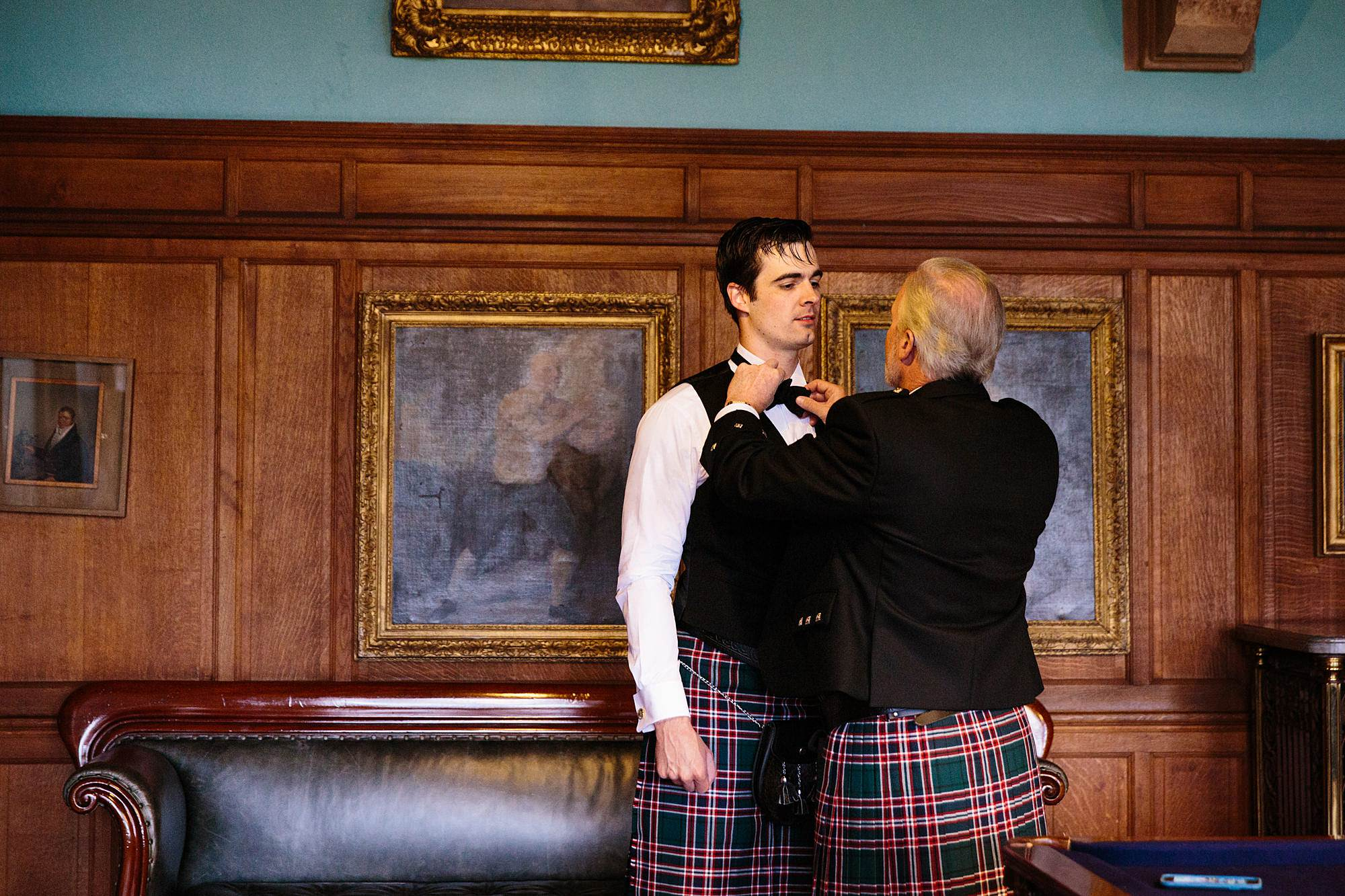 intimate wedding scotland groomsman gets his tie adjusted