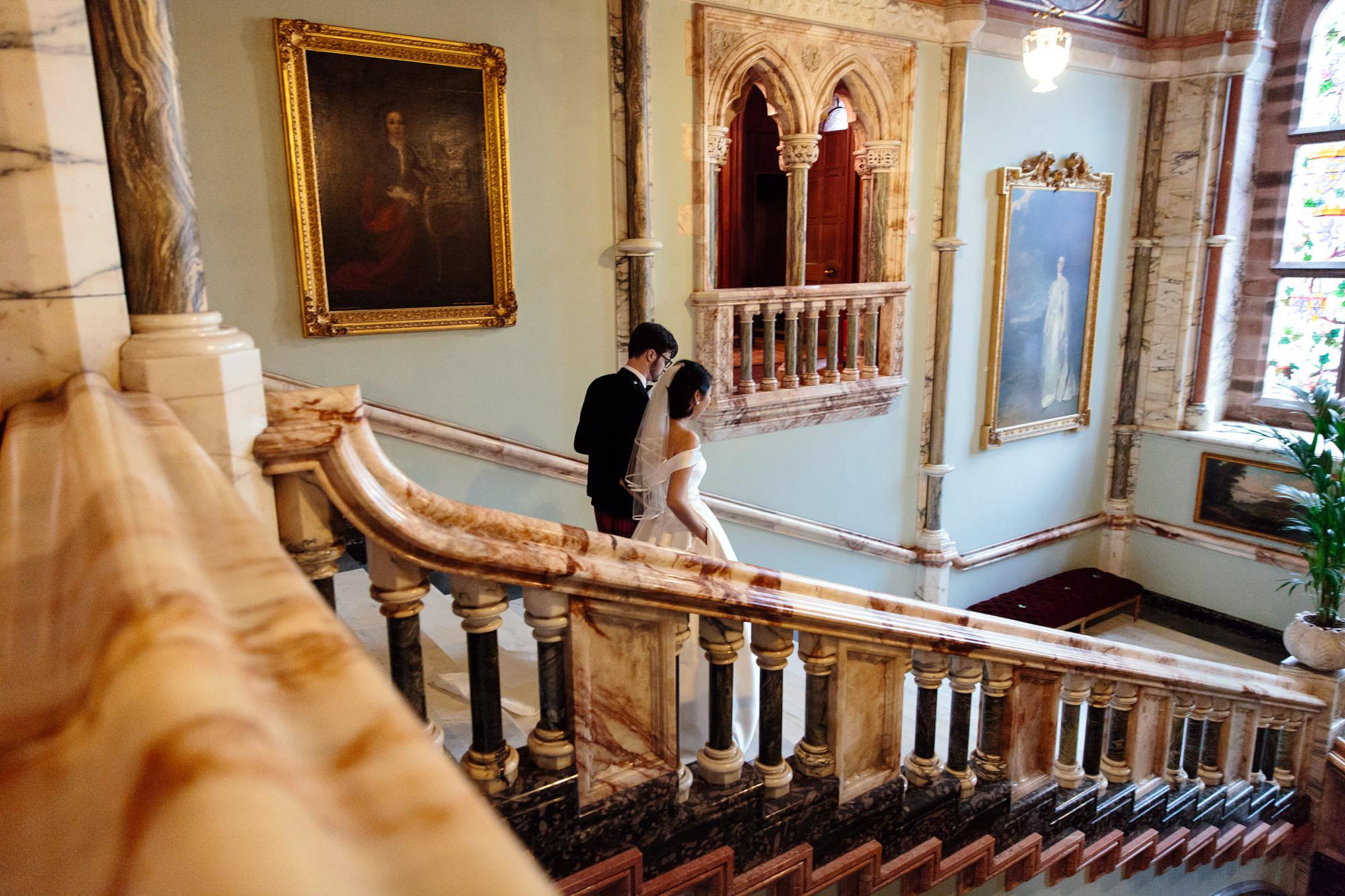 intimate wedding scotland bride and groom walking down staircase