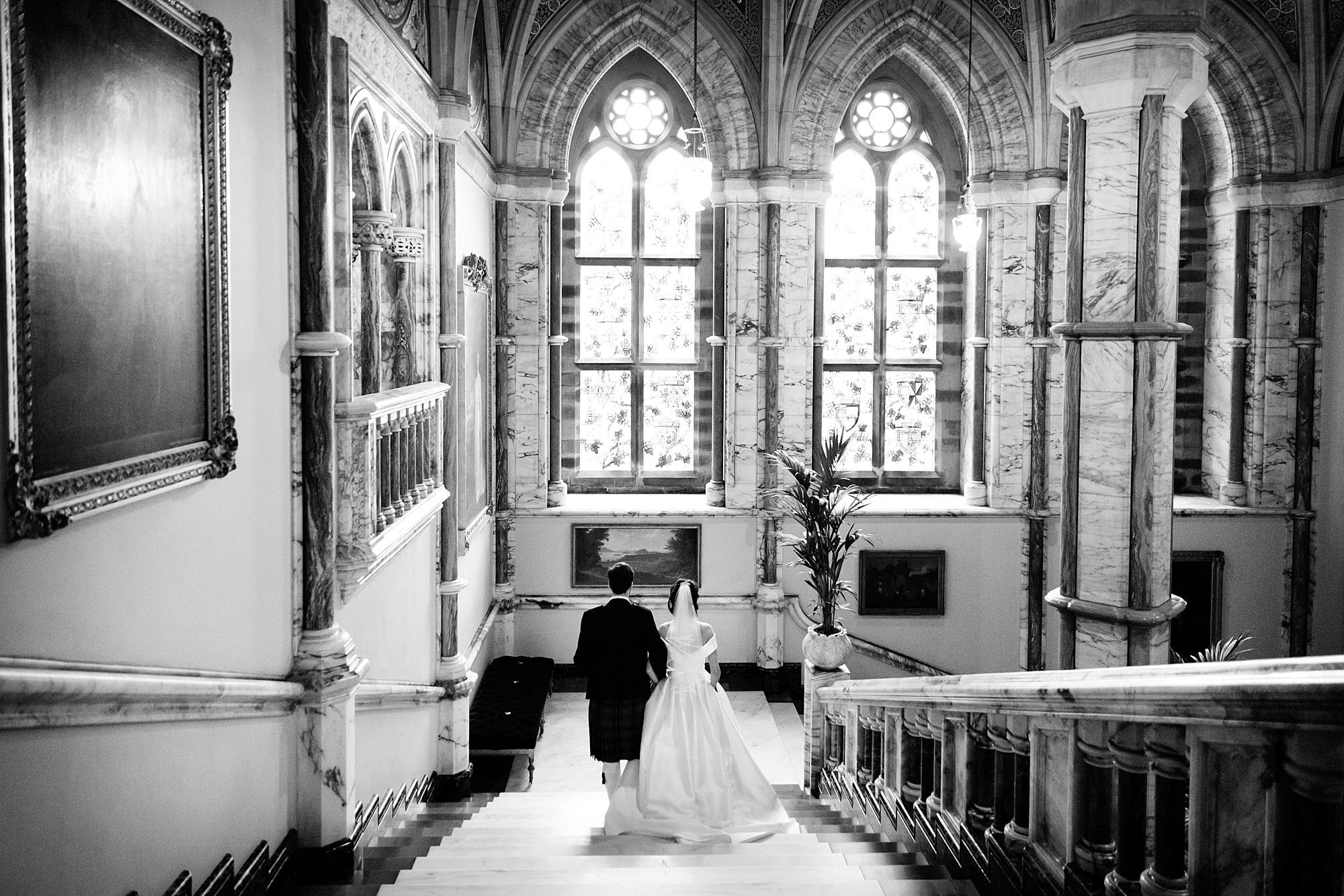 intimate wedding scotland groom and bride walk down grand stairs