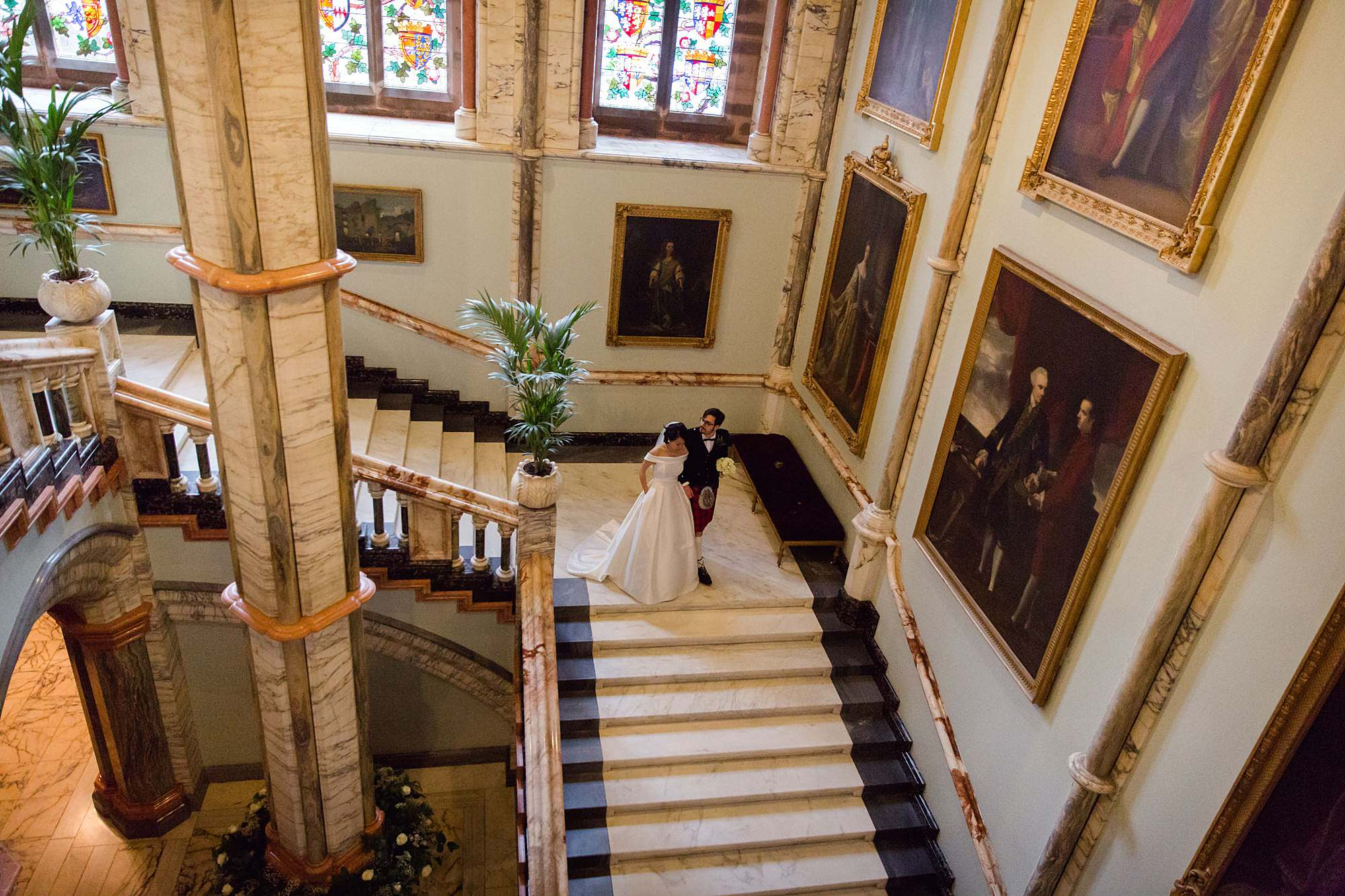intimate wedding scotland groom and bride walking down staircase