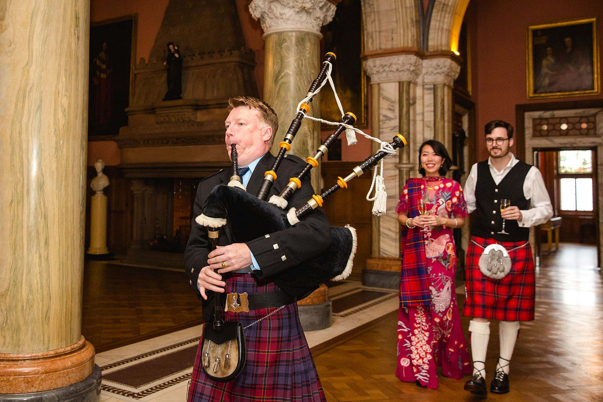 intimate wedding scotland bagpiper leading bride and groom