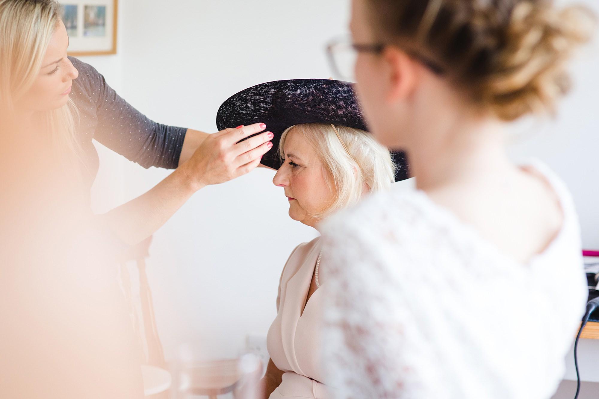 Lillibrooke Manor wedding mother of bride having hat adjusted