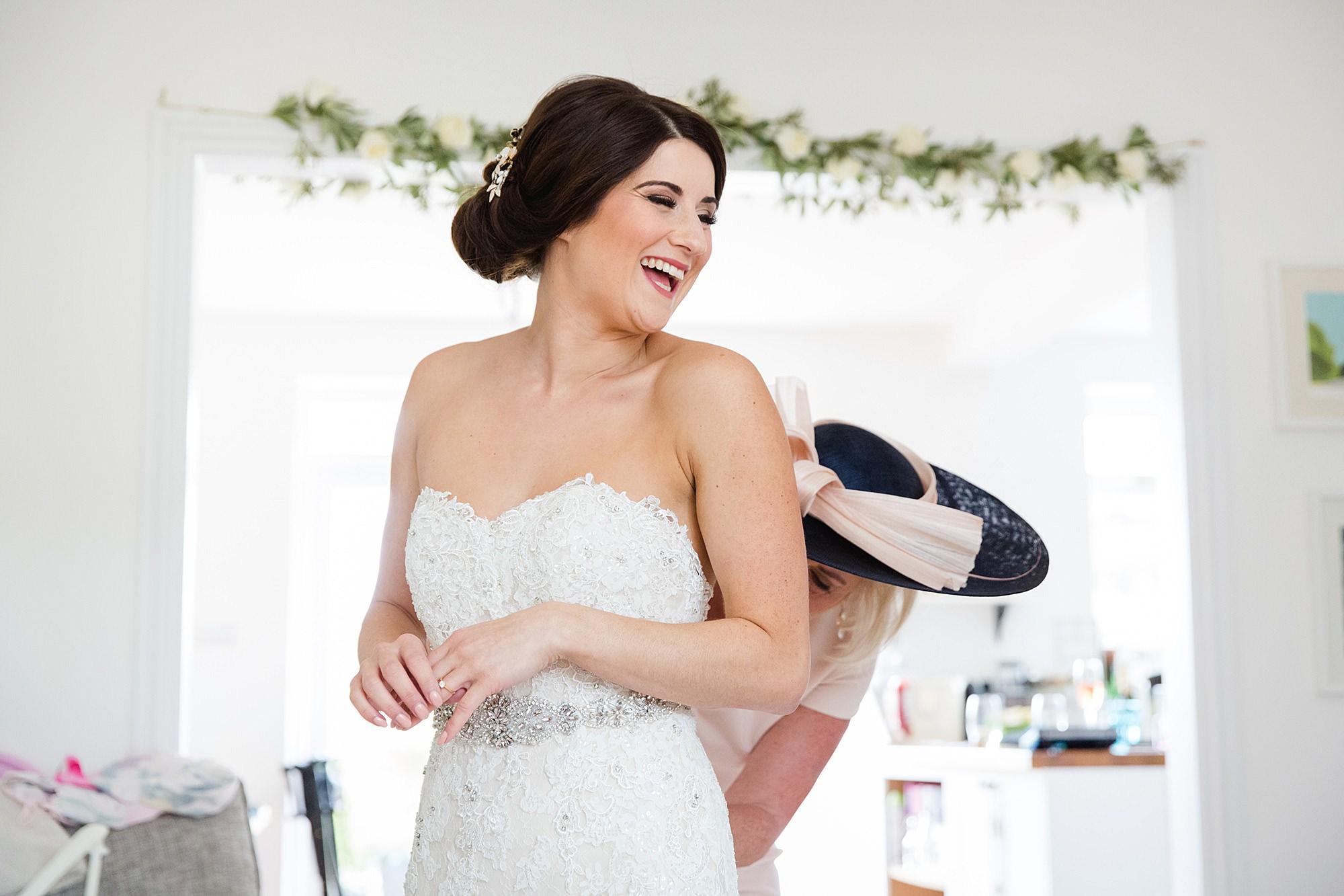 Lillibrooke Manor wedding bride laughs as mother adjusts her dress