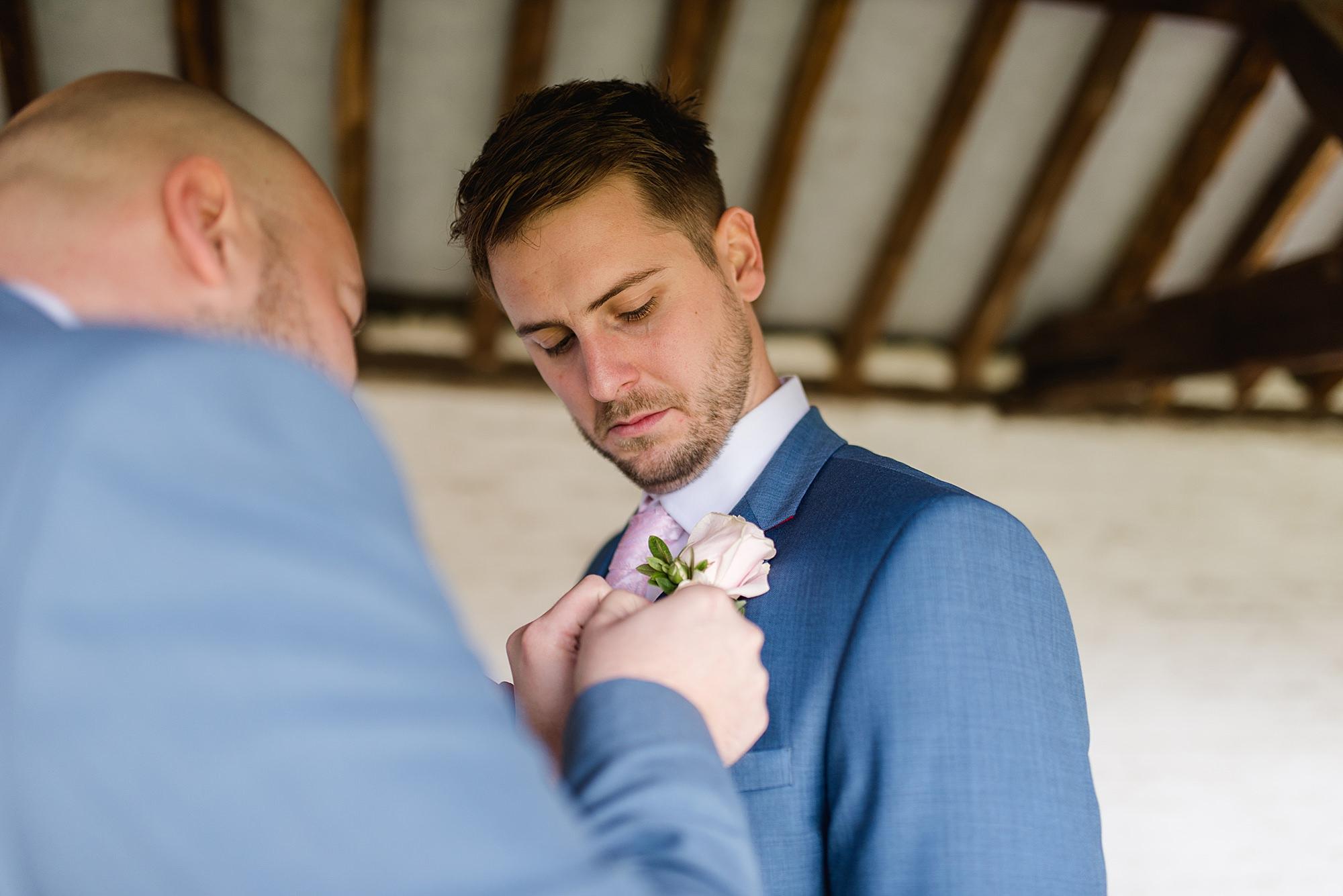Lillibrooke Manor wedding best man puts buttonhole on groom