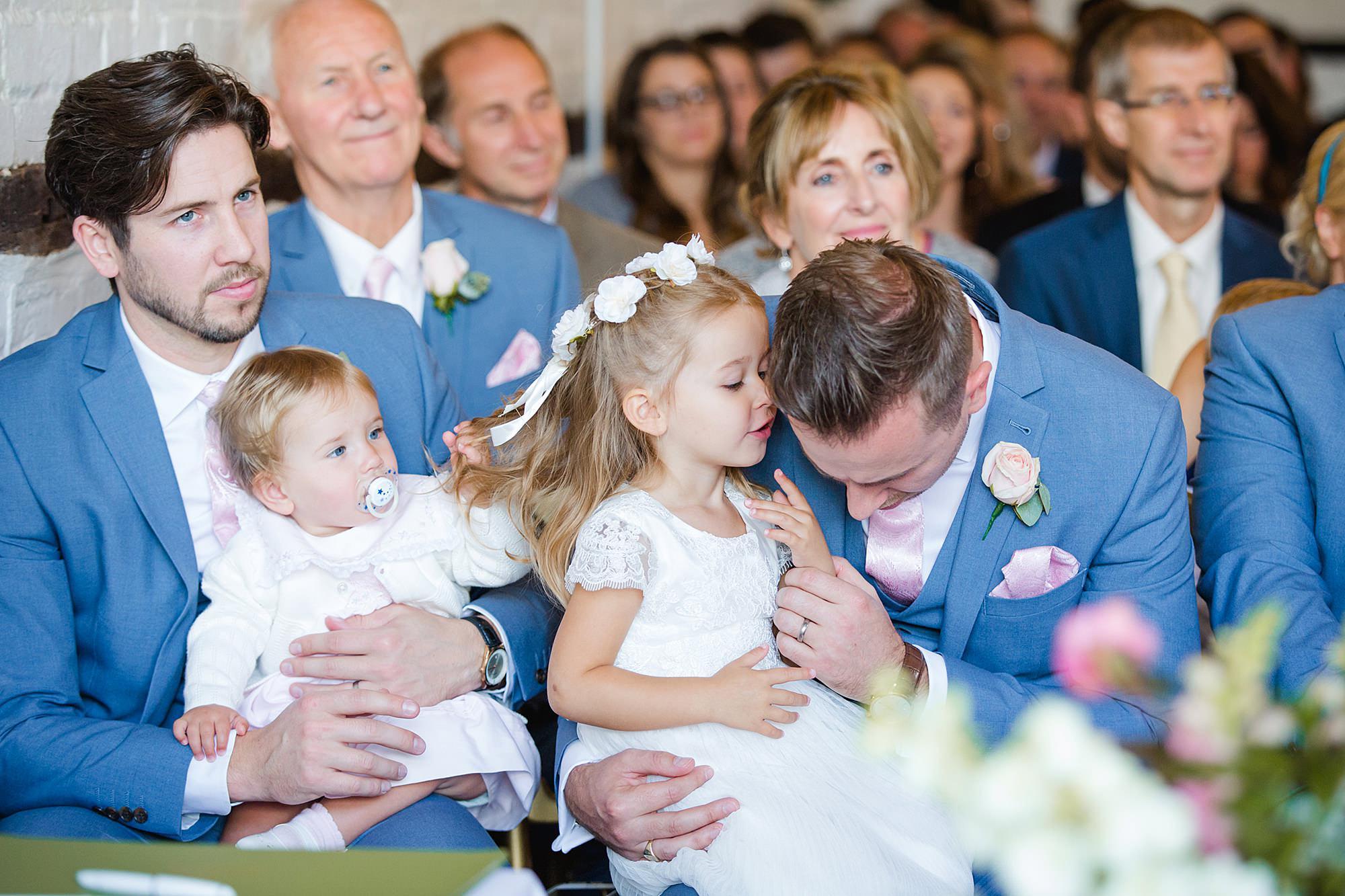 Lillibrooke Manor wedding flower girl whispering to groomsman