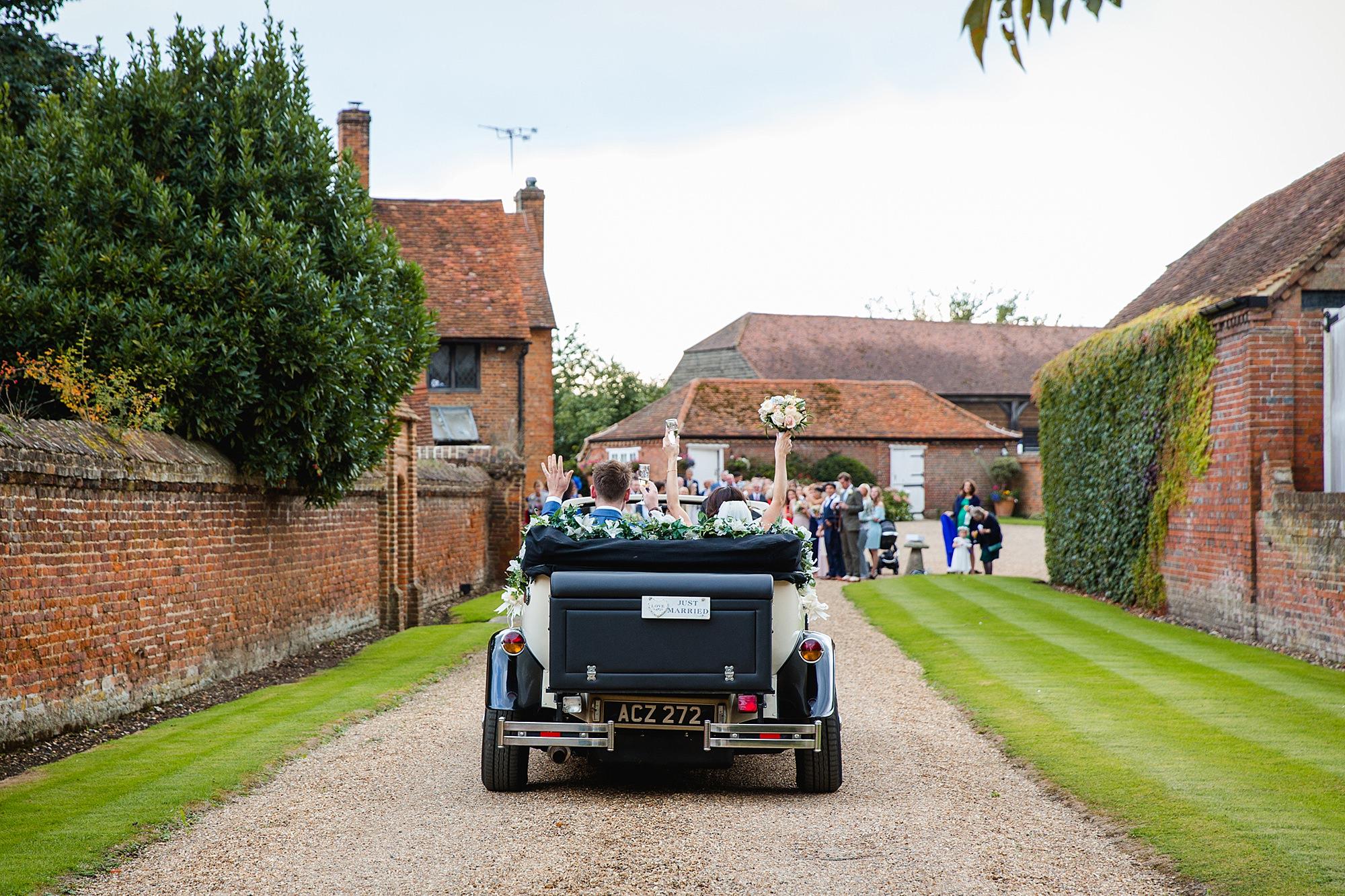 Lillibrooke Manor wedding bride and groom drive towards wedding guests