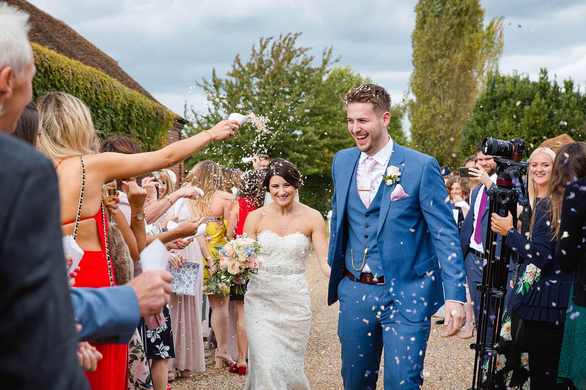 Lillibrooke Manor wedding bride and groom walk through confetti