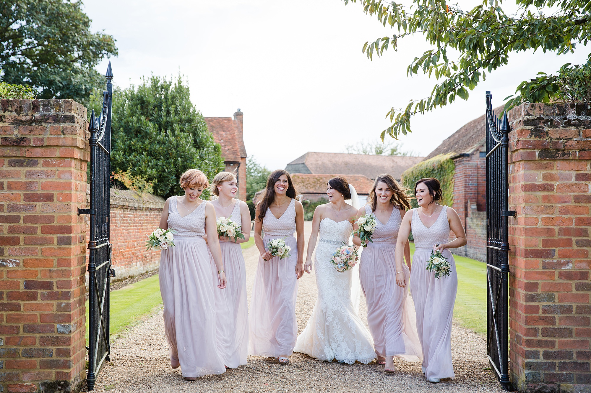 Lillibrooke Manor wedding bride and bridesmaids laugh and walk together
