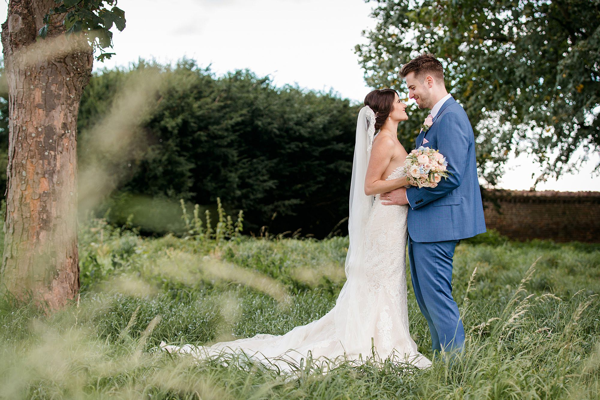 Lillibrooke Manor wedding bride and groom laugh at each other in wild garden