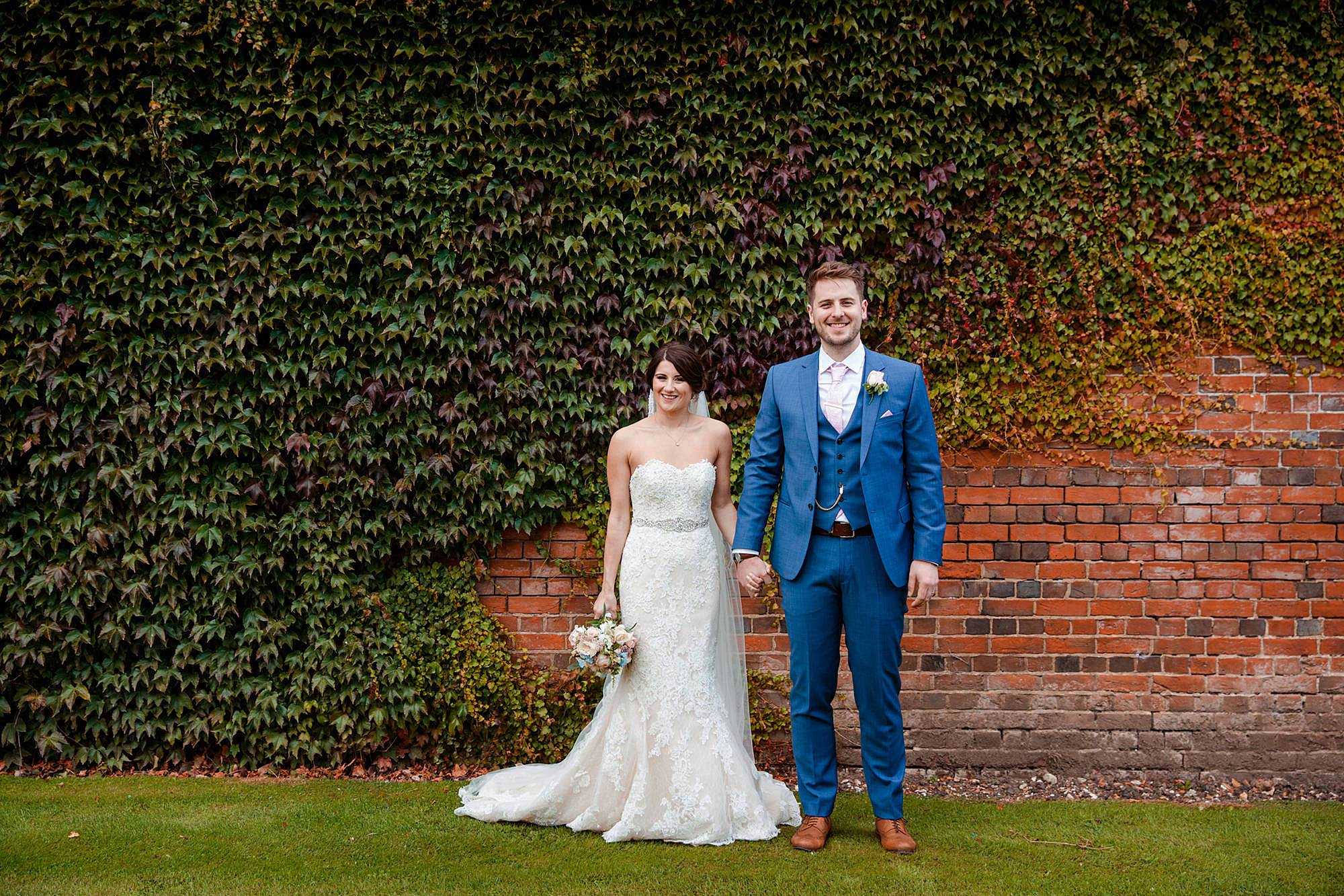 Lillibrooke Manor wedding bride and groom laugh together by wall