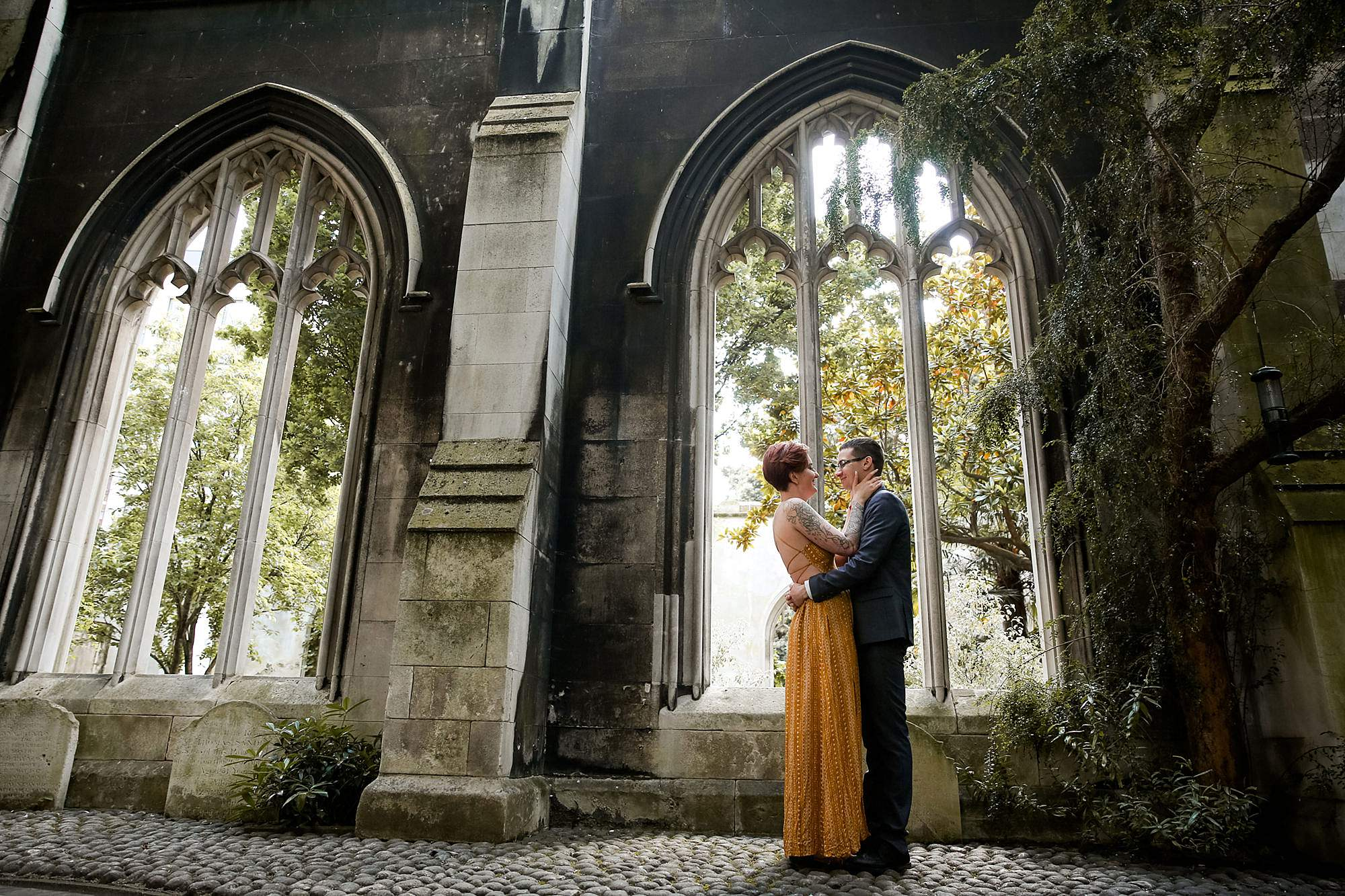 london engagement session couple stands together in front of church ruins