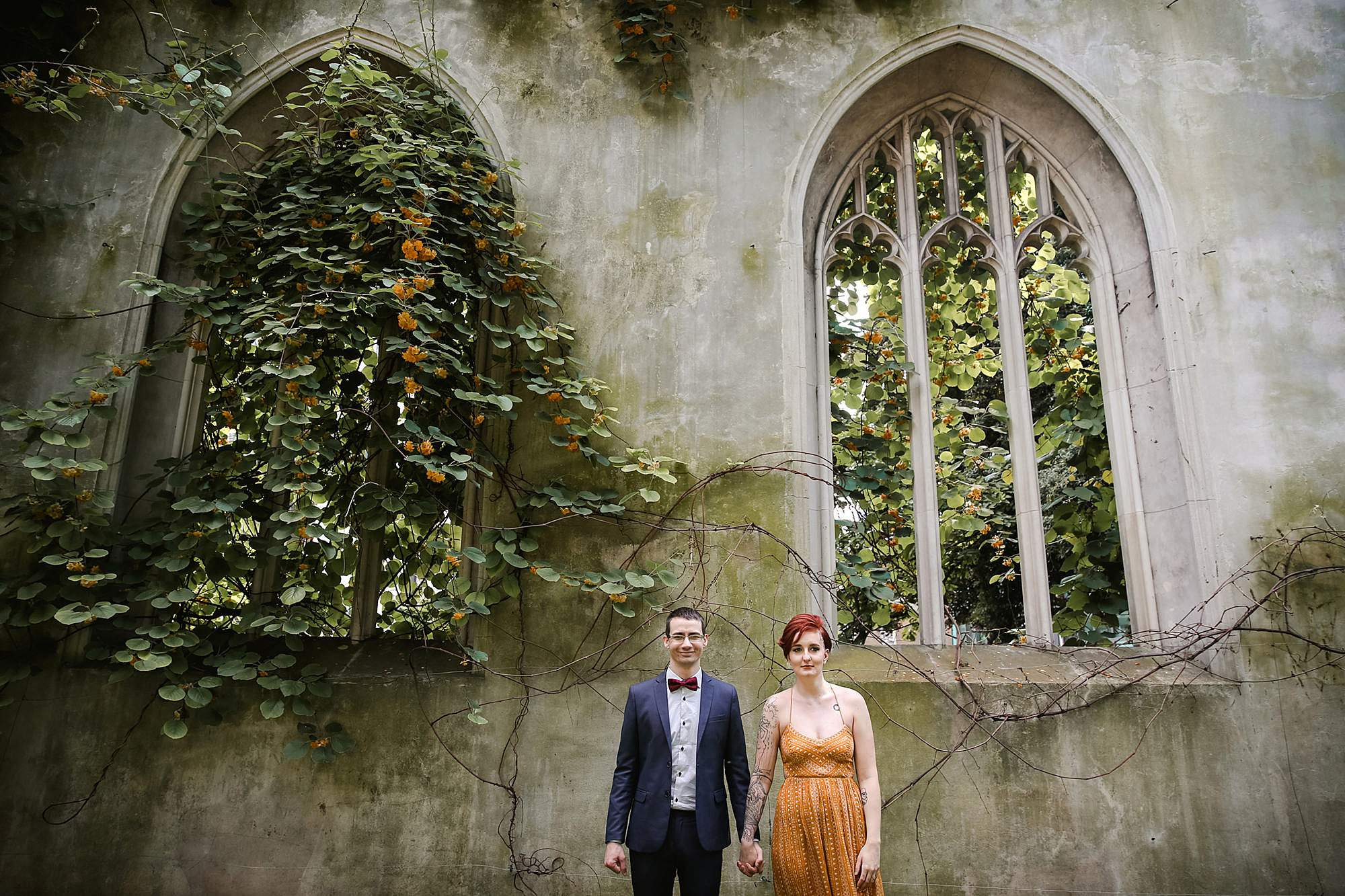 london engagement session portrait of couple in front of overgrown windows