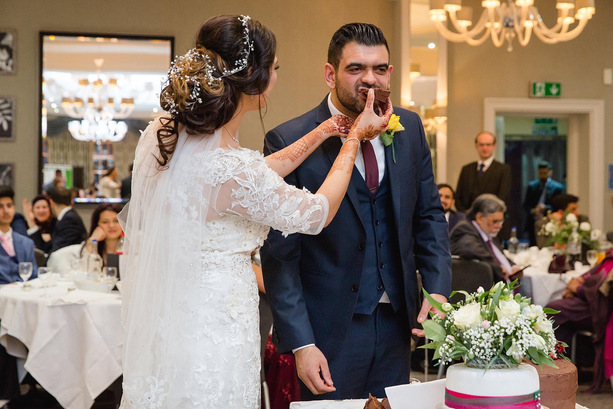 Richmond Hill Hotel wedding bride feeds groom wedding cake