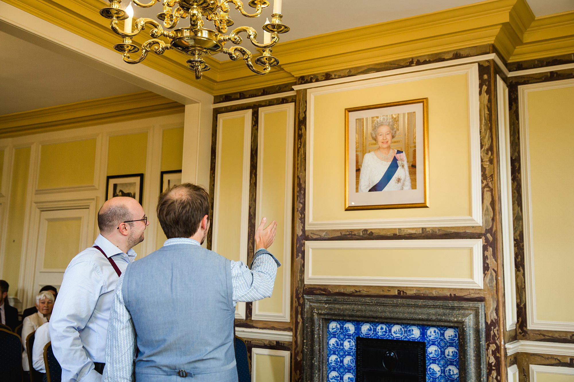 Fun village hall wedding groom and best man looking at a portrait of the Queen