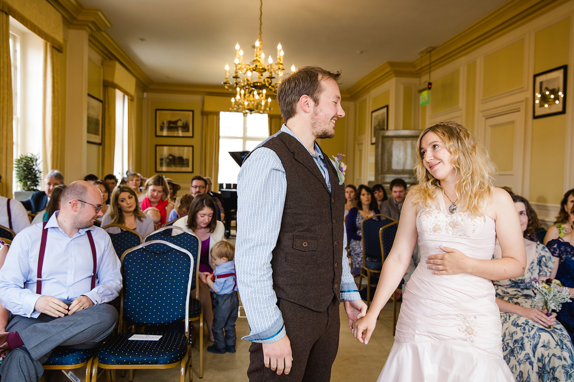 Fun village hall wedding portrait of bride and groom during wedding ceremony at Edes House