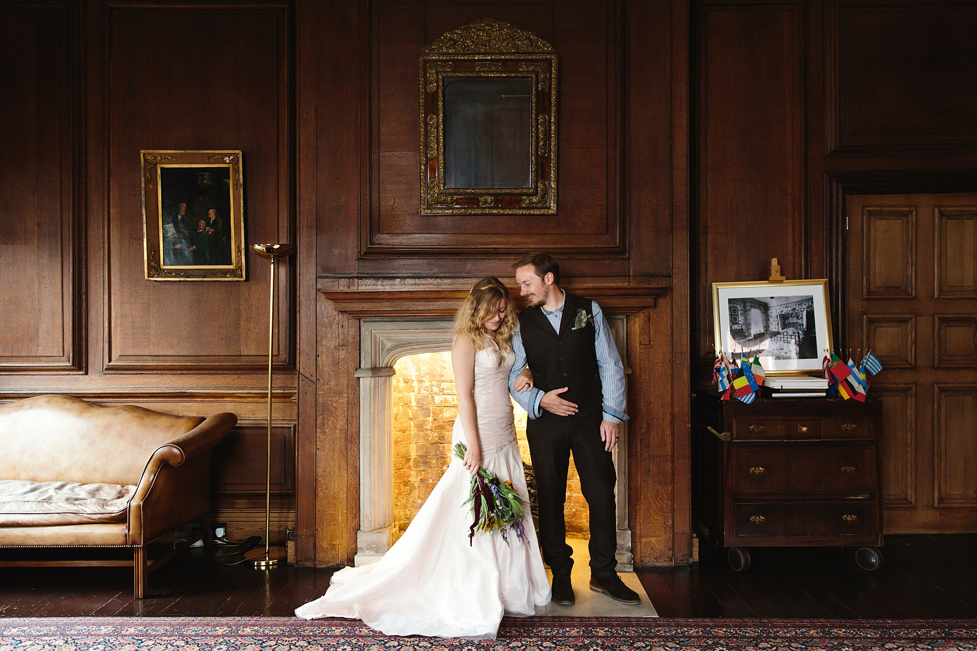 Fun village hall wedding bride and groom by fireplace at Edes House