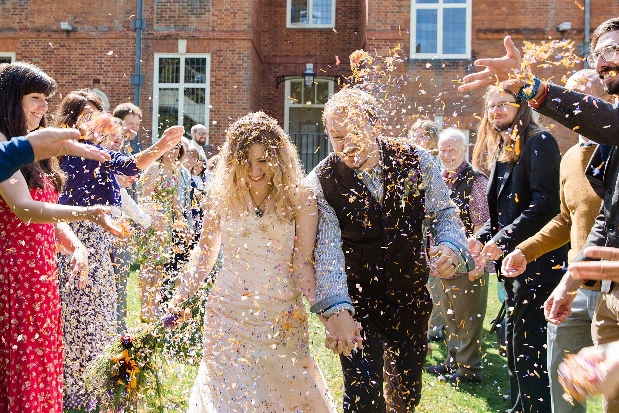 Fun village hall wedding bride and groom walk through confetti