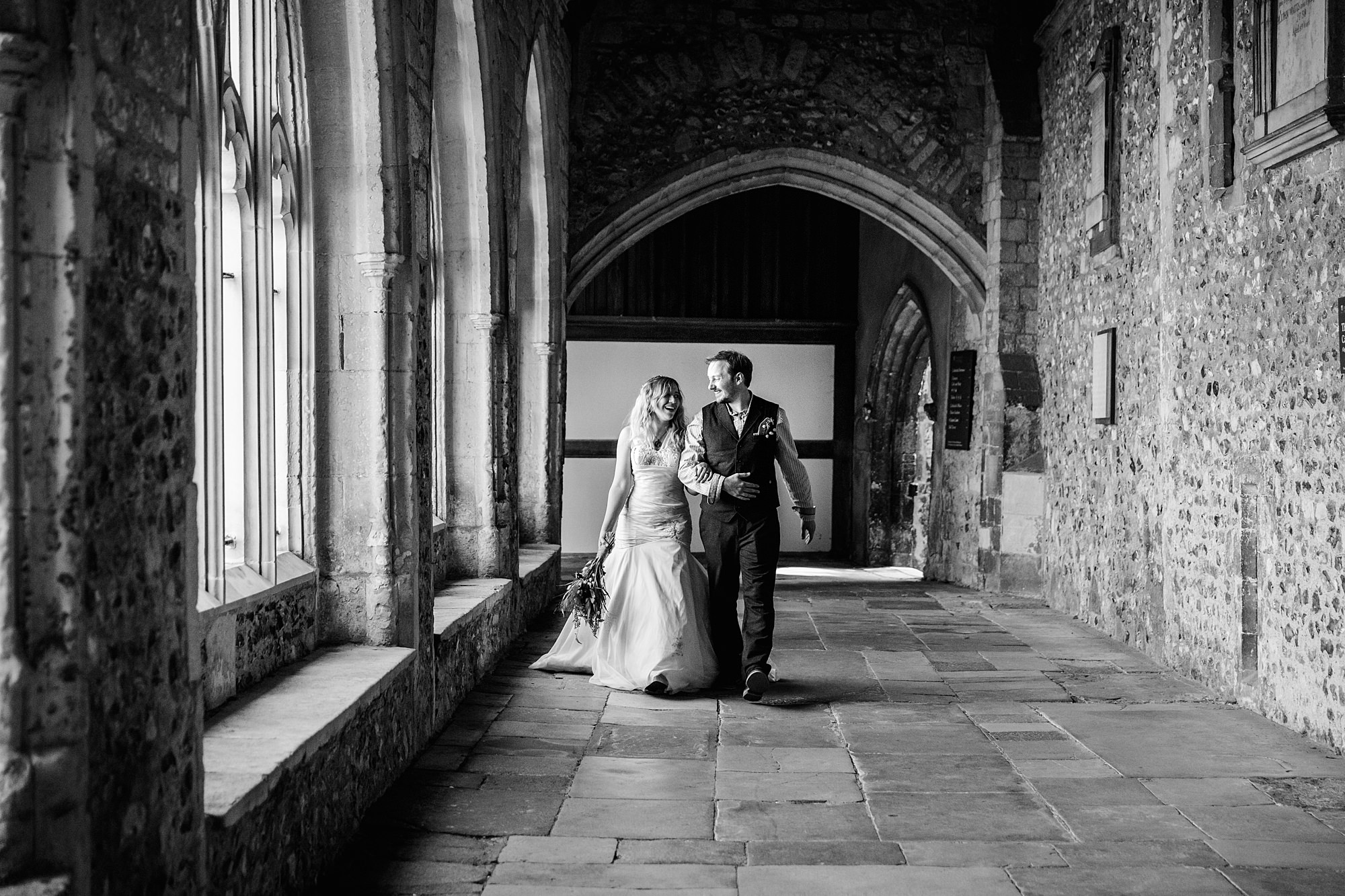 Fun village hall wedding bride and groom in cloisters of cathedral