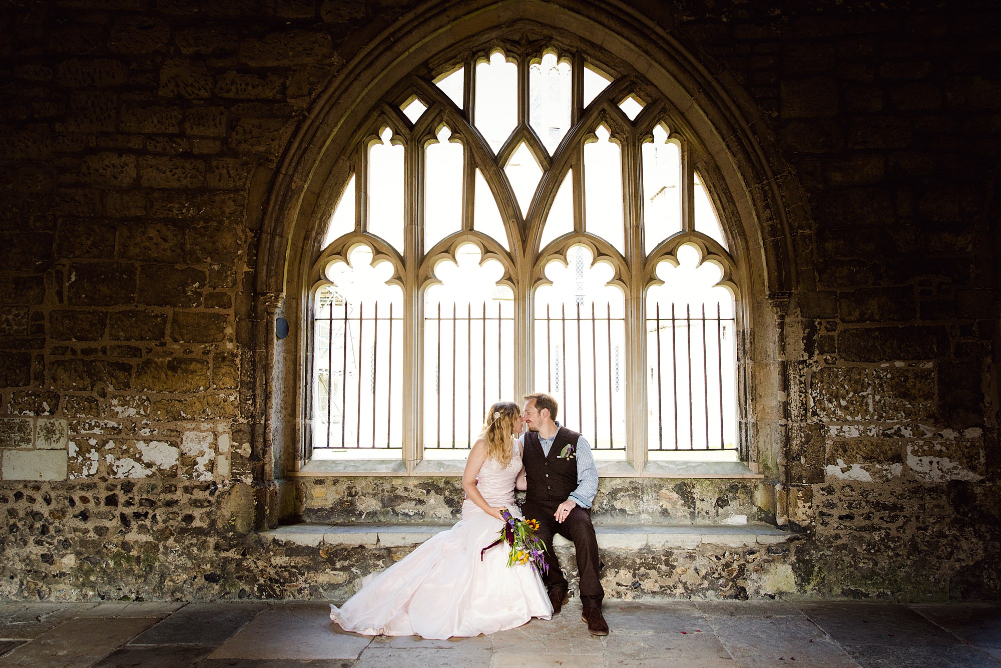 Fun village hall wedding bride and groom in cloisters window