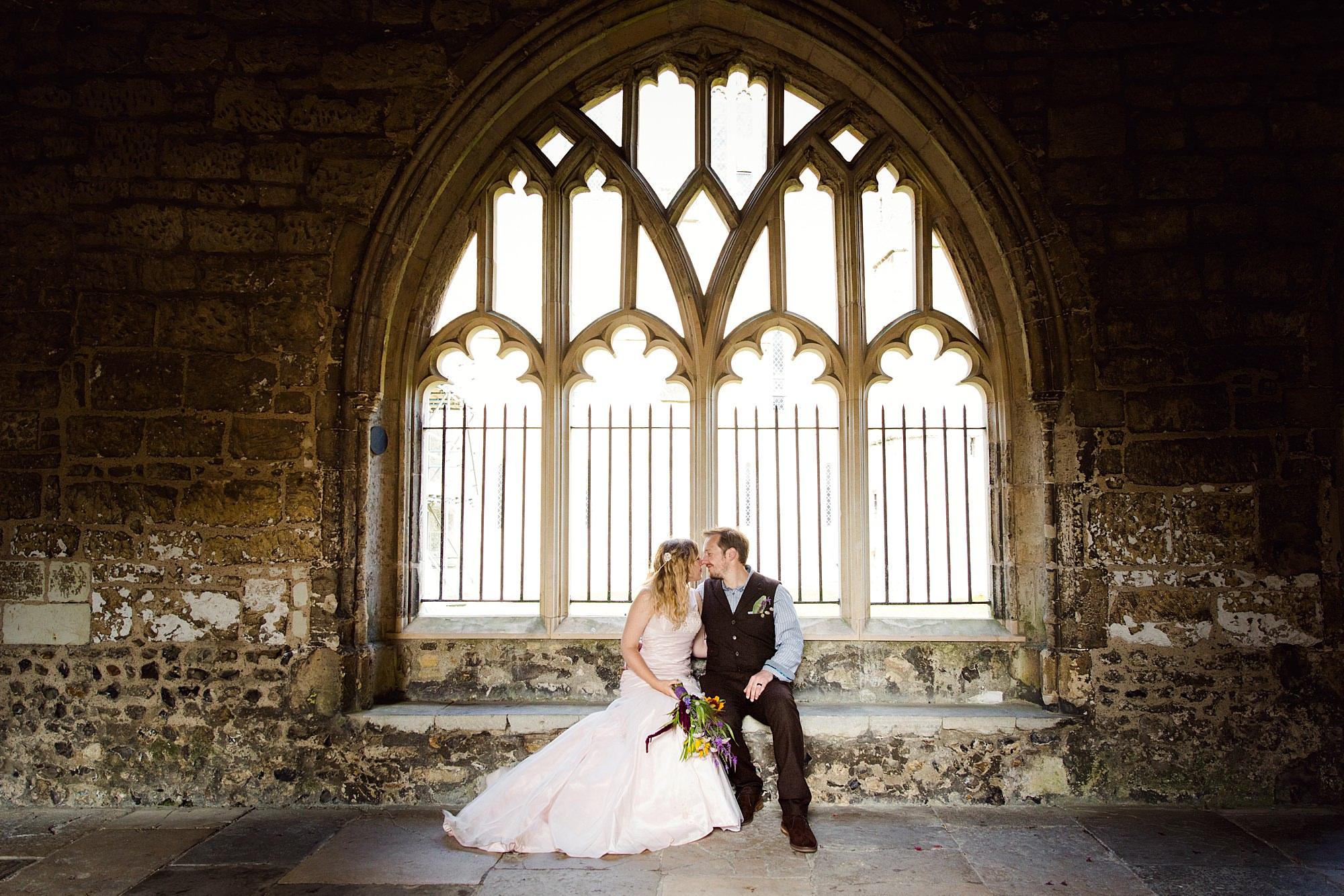 Fun village hall wedding bride and groom in cloisters window