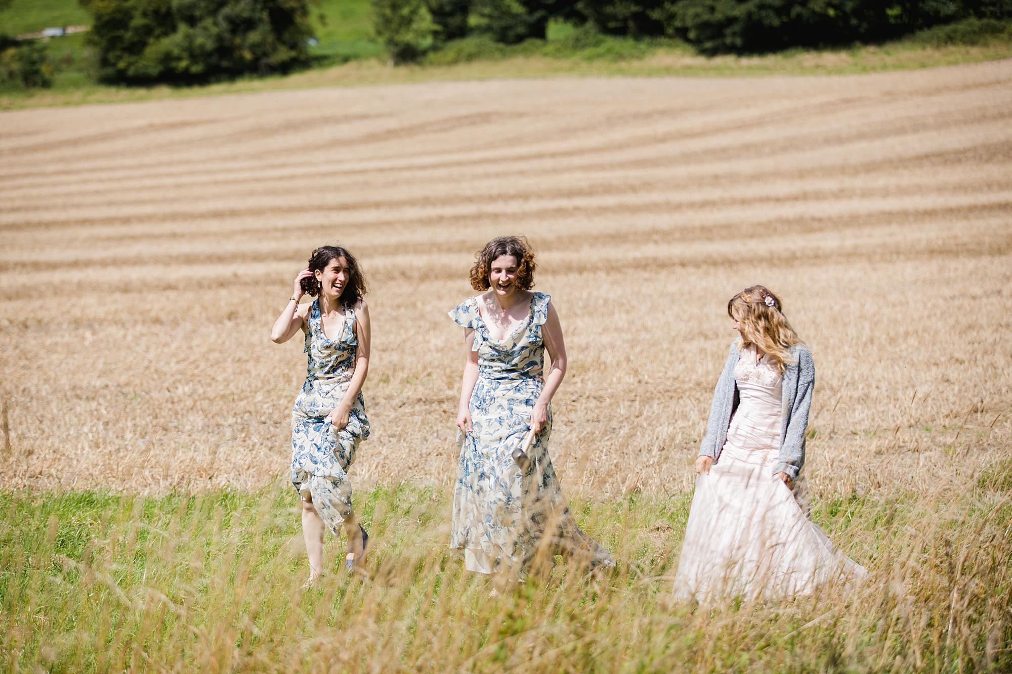 Fun village hall wedding bride and bridesmaids walking in a field