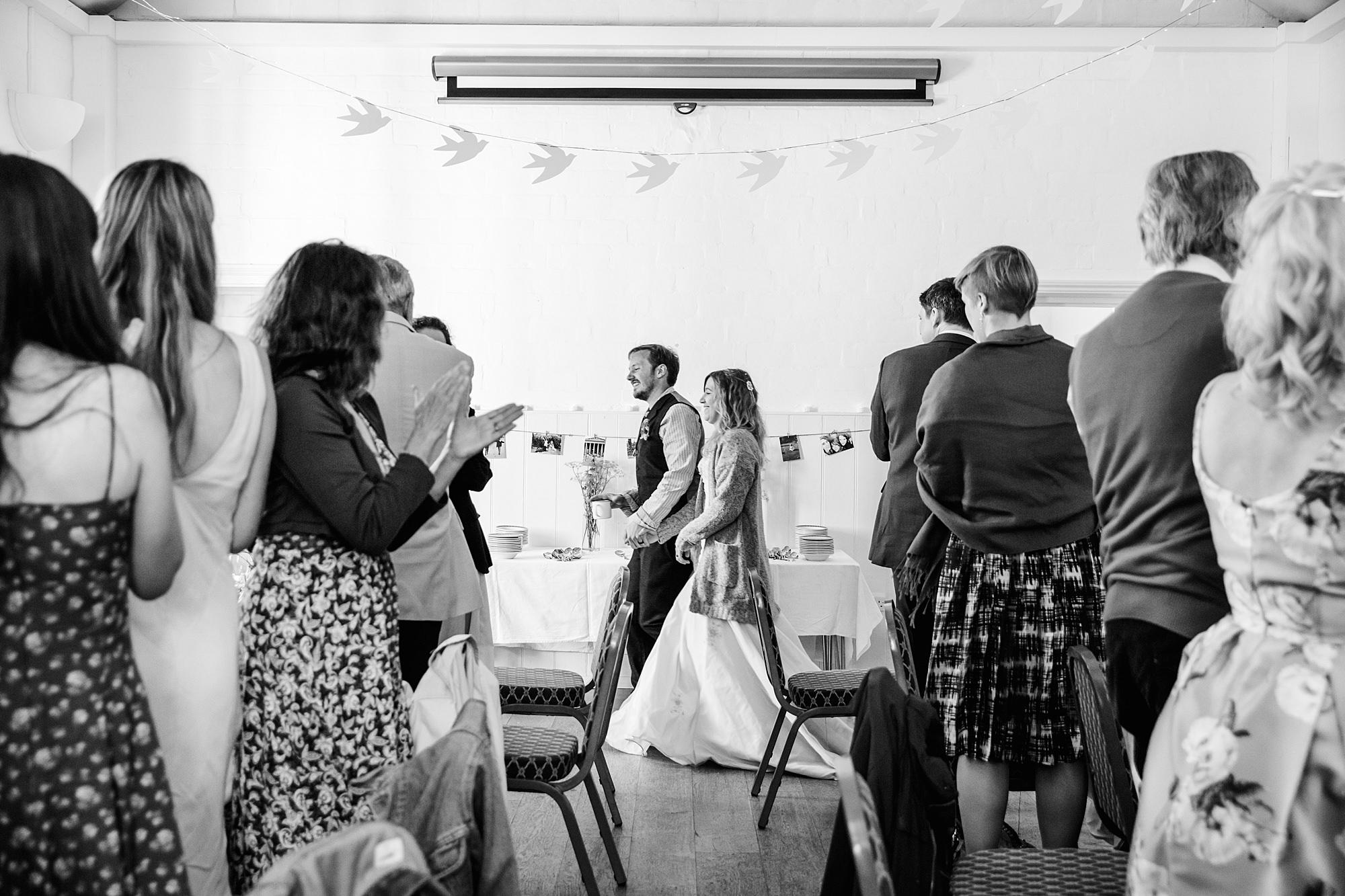 Fun village hall wedding guests cheer in bride and groom's entrance
