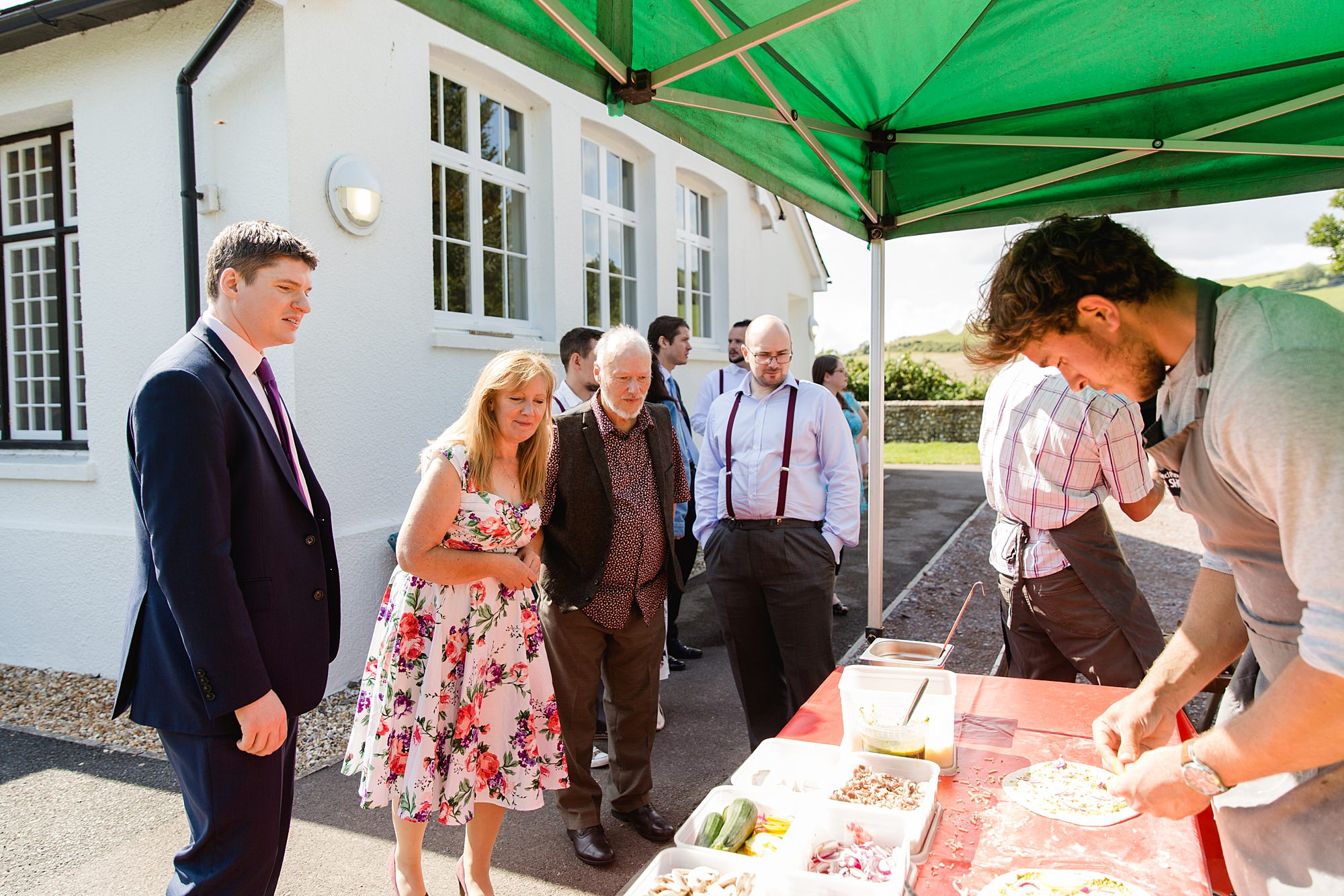 Fun village hall wedding guests enjoying pizza van