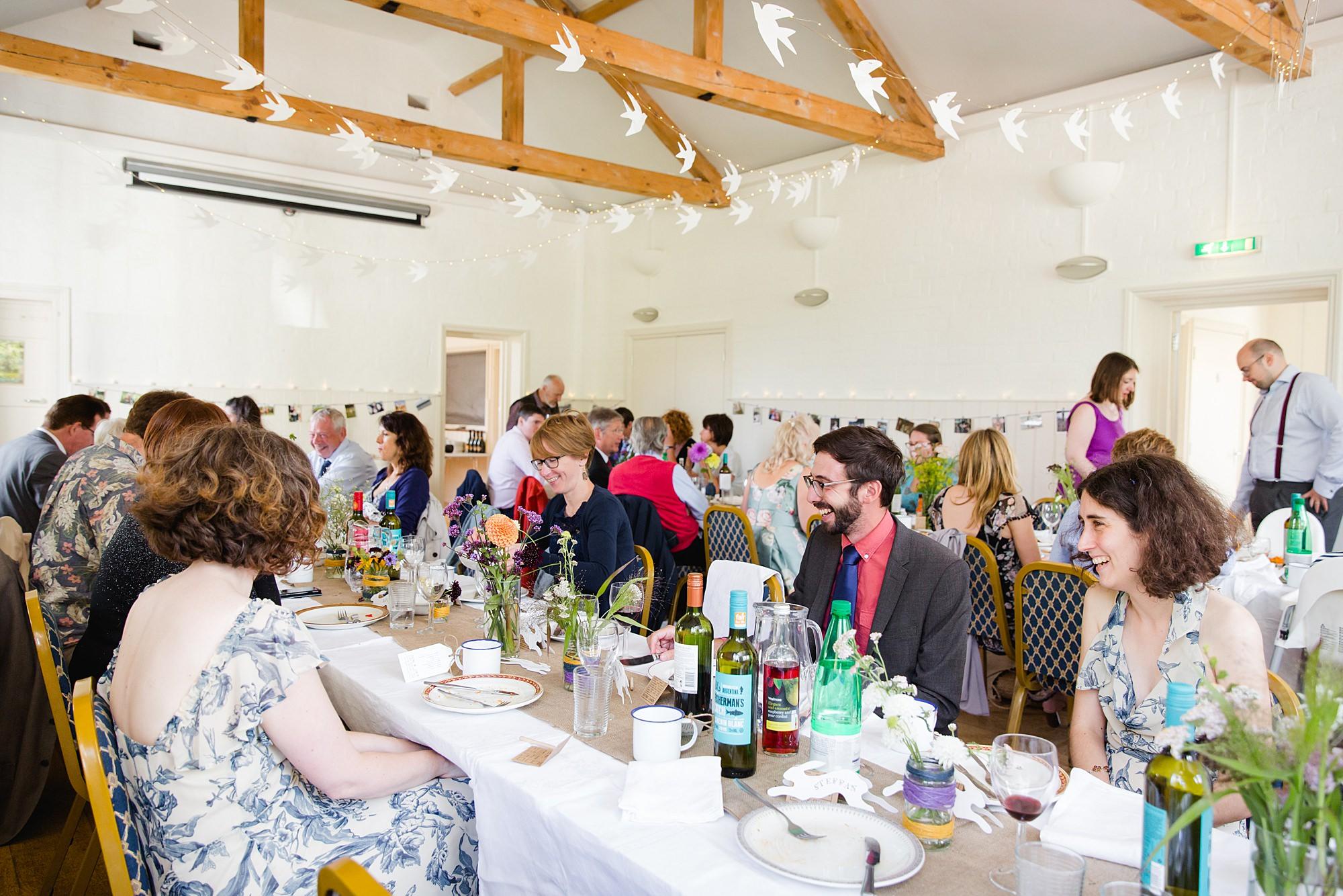 Fun village hall wedding guests enjoying lunch